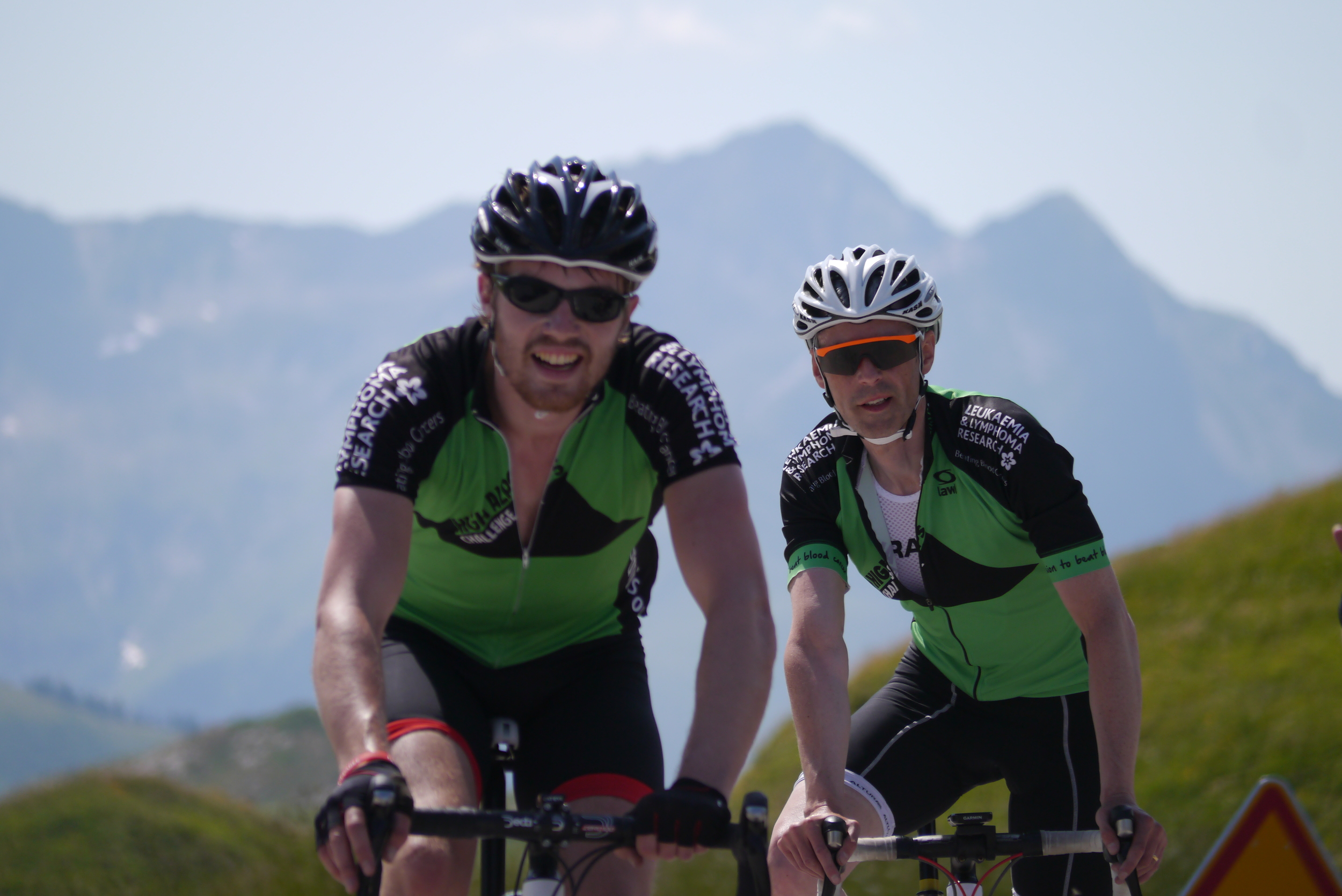 Andrew cycled across the alps, just to have the opportunity to photobomb Simon's moment of glory