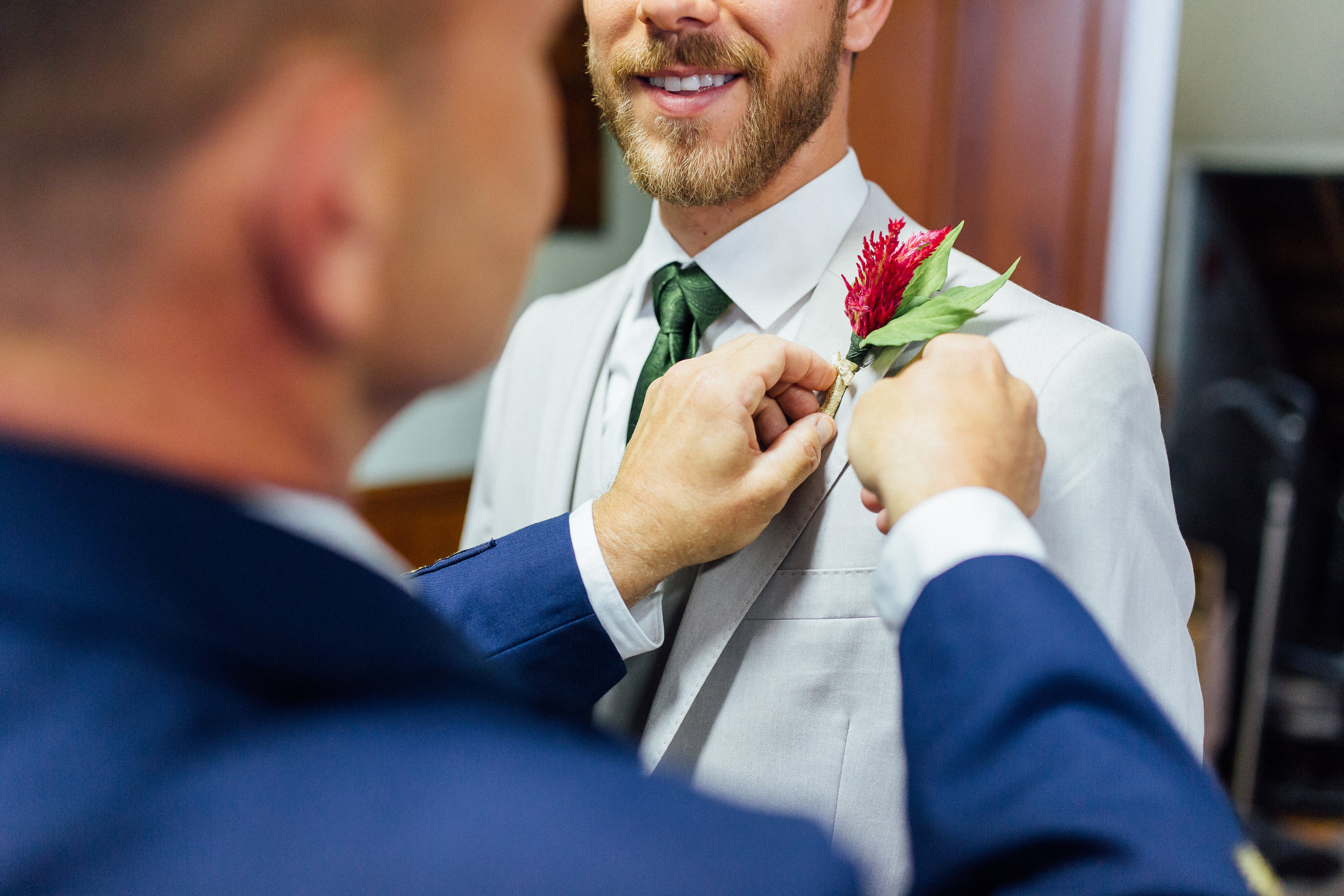 Groom's father putting on his boutonnière and smiling