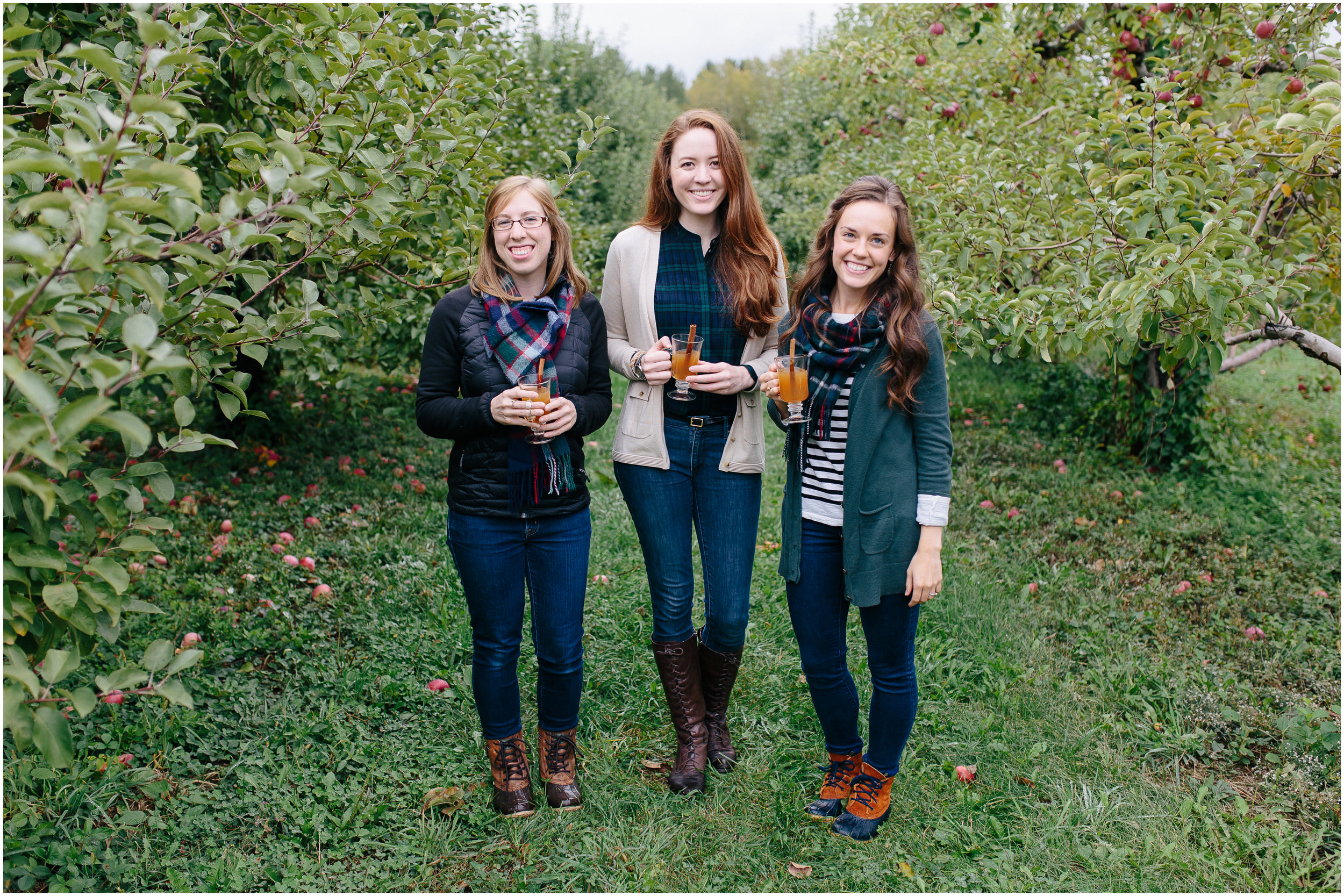 Girl friends smiling in an apple orchard, holding hot apple cider with cinnamon sticks, cute scarves, trendy