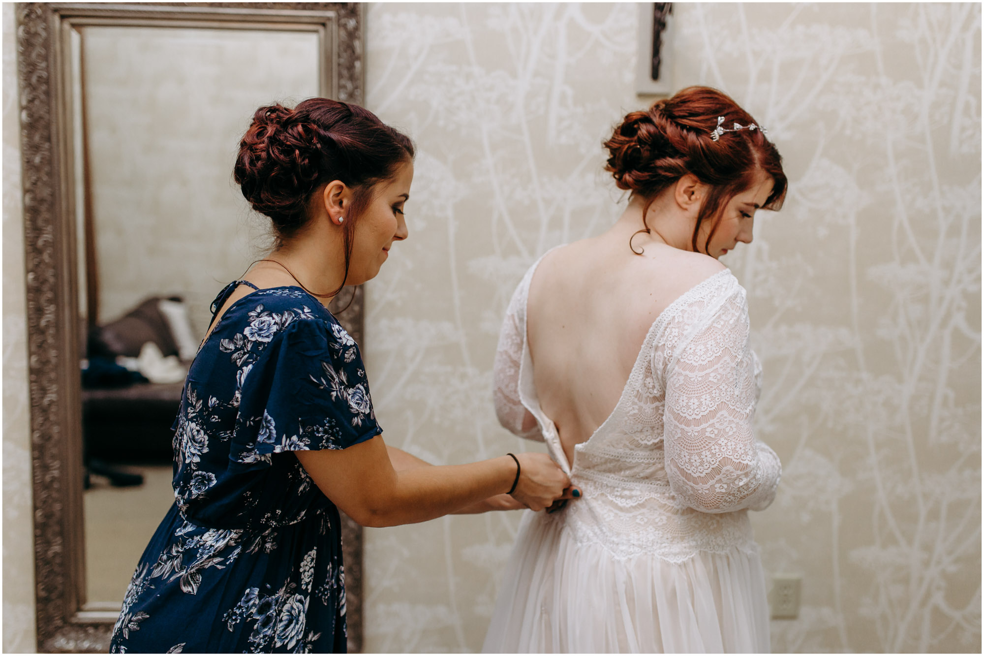 Maid of honor zipping bride's wedding dress - by Ashleigh Laureen Photography at LaBelle Winery in Amherst, New Hampshire.