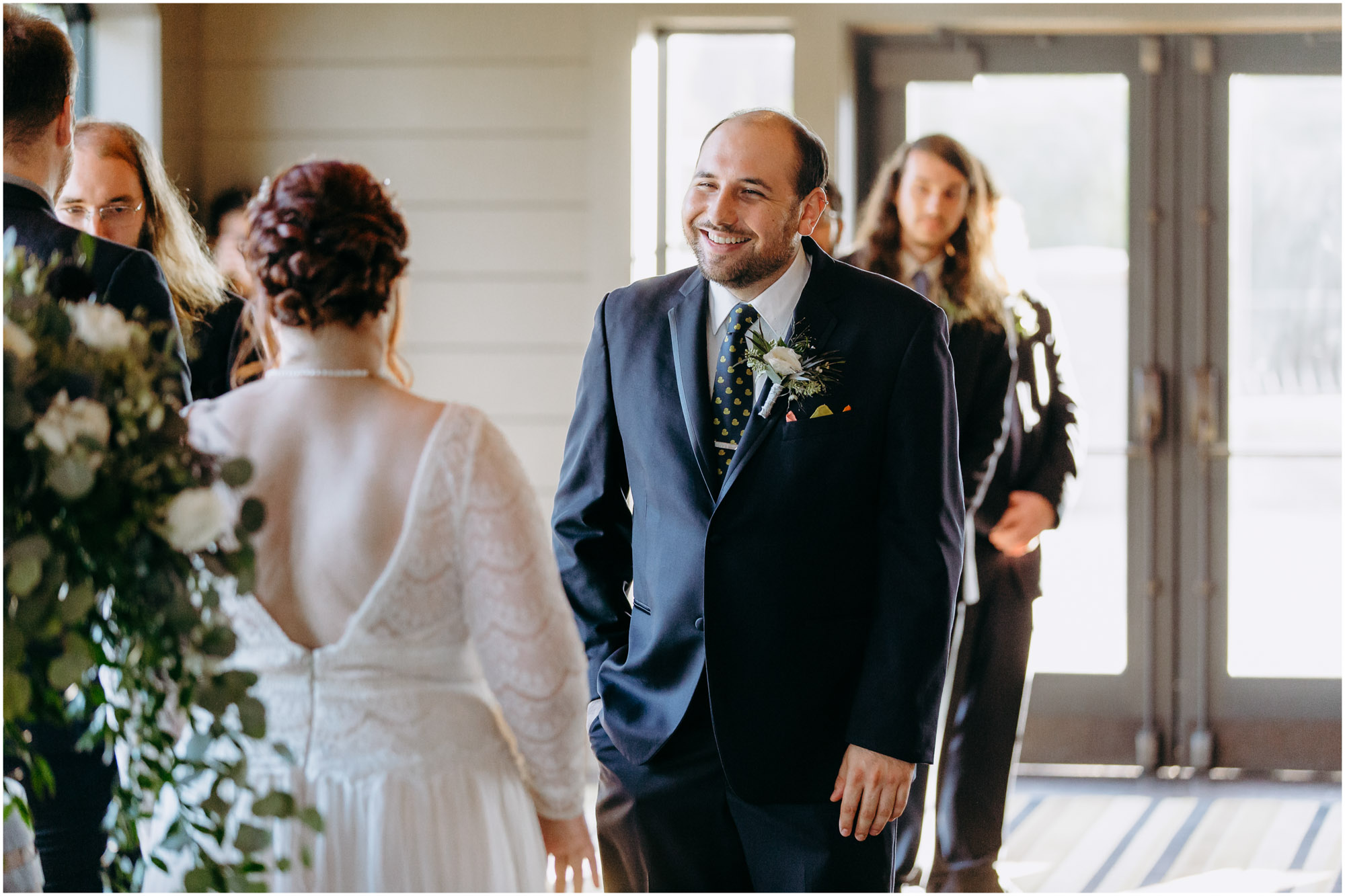 Smiling groom during ceremony - by Ashleigh Laureen Photography at LaBelle Winery in Amherst, New Hampshire