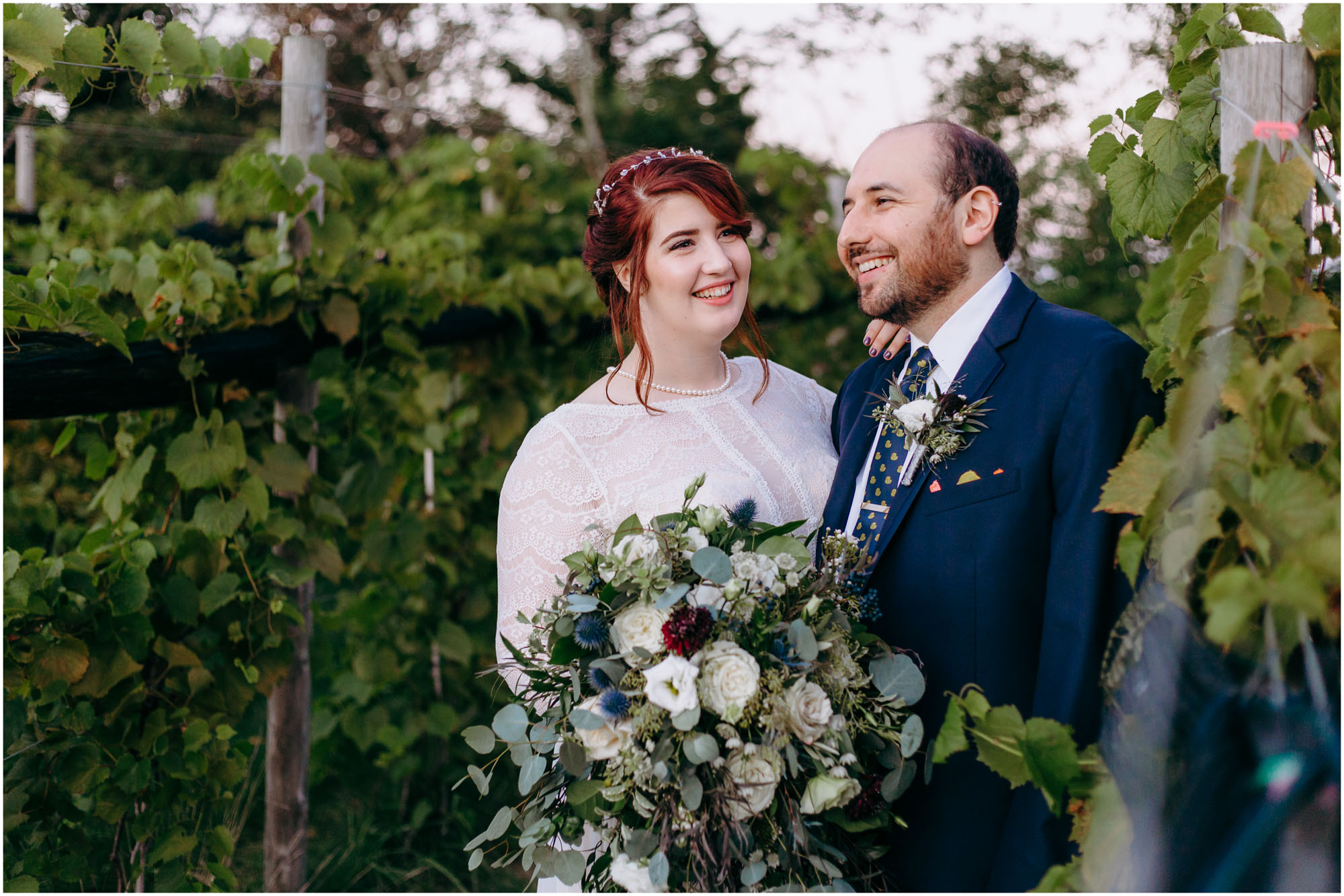 Trendy, hipster bride and groom smiling in vineyard - by Ashleigh Laureen Photography at LaBelle Winery in Amherst, New Hampshire