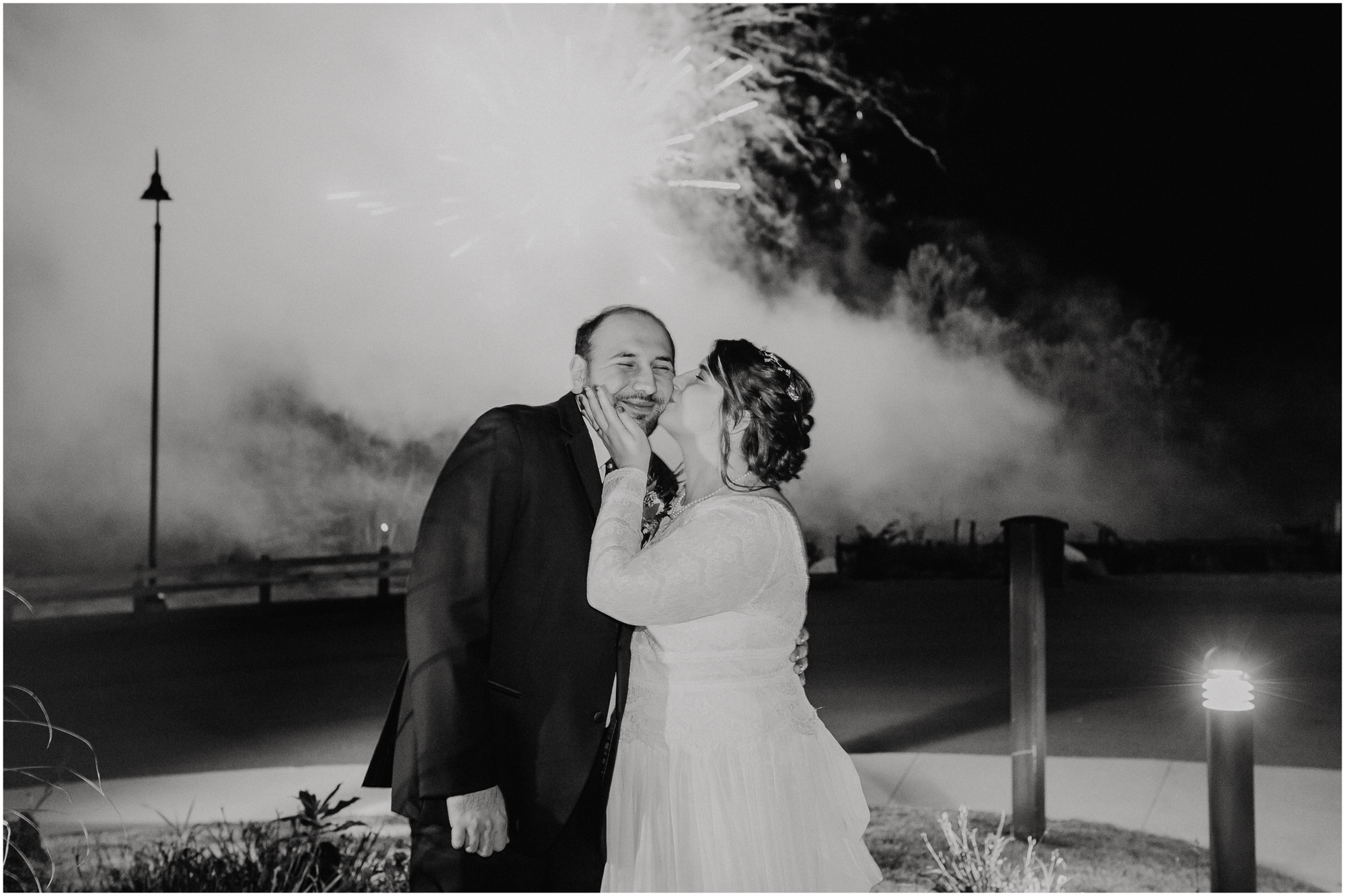 Bride kisses groom's cheek under fireworks during wedding reception - by Ashleigh Laureen Photography at LaBelle Winery in Amherst, New Hampshire