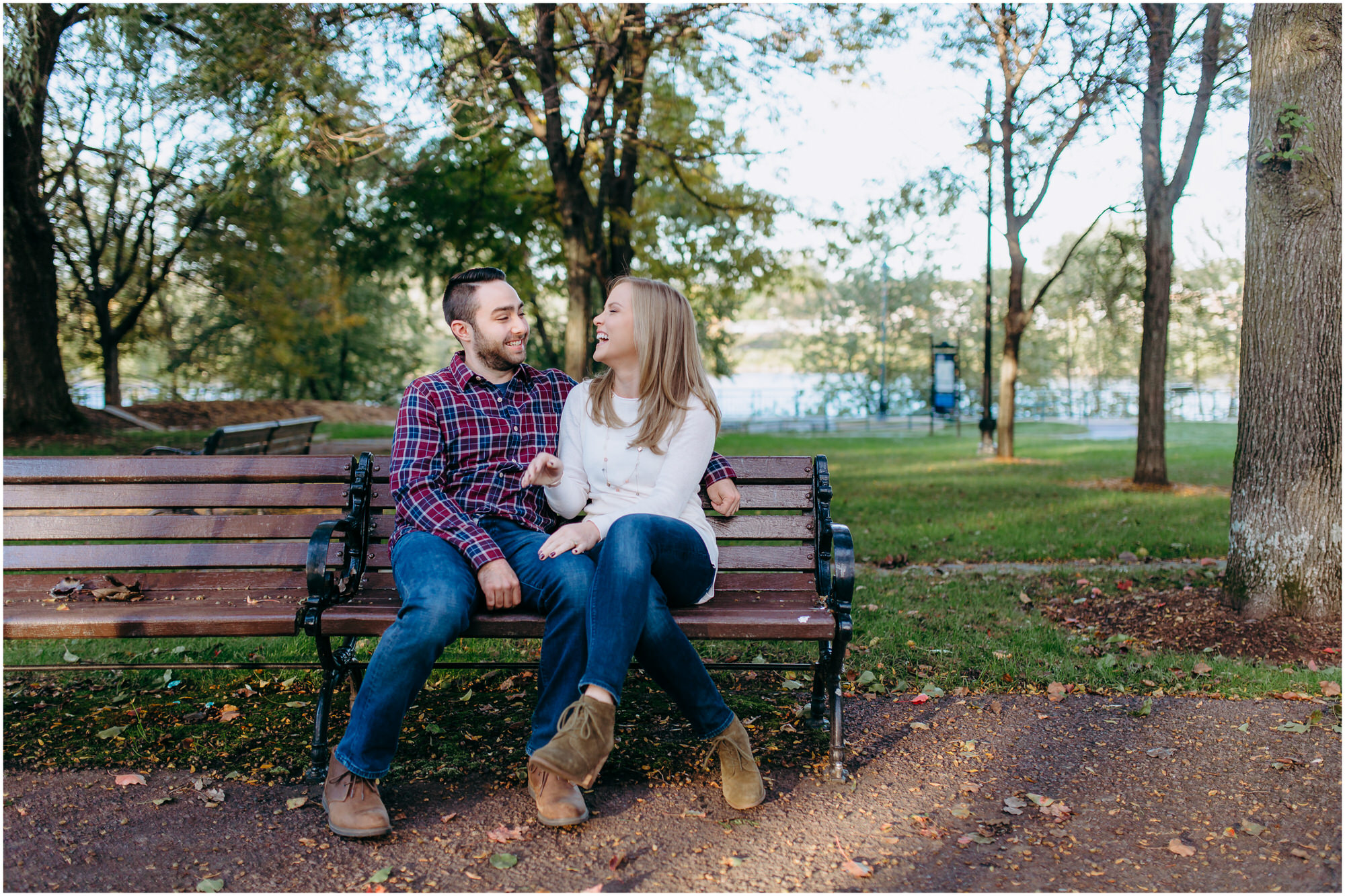 Happy couple sits snuggling and laughing on a park bench - by New Hampshire wedding photographer Ashleigh Laureen Photography in Lowell, Massachusetts