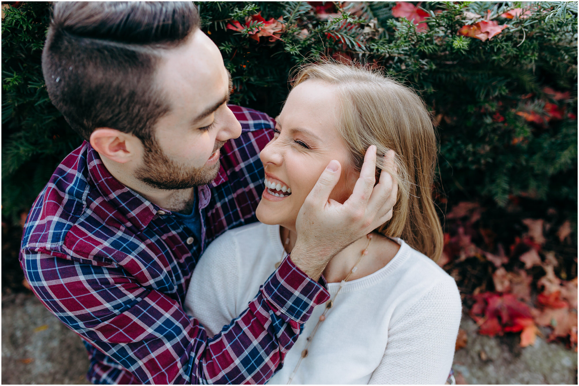 Beautiful couple snuggles in a park, man pushes hair back from his fiancee's face before he kisses her - by New Hampshire wedding photographer Ashleigh Laureen Photography in Lowell, Massachusetts