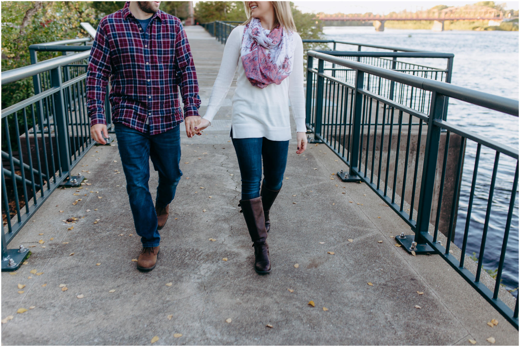 Adventurous couple walks hand-in-hand along the riverside for the engagement photos - by New Hampshire wedding photographer Ashleigh Laureen Photography in Lowell, Massachusetts