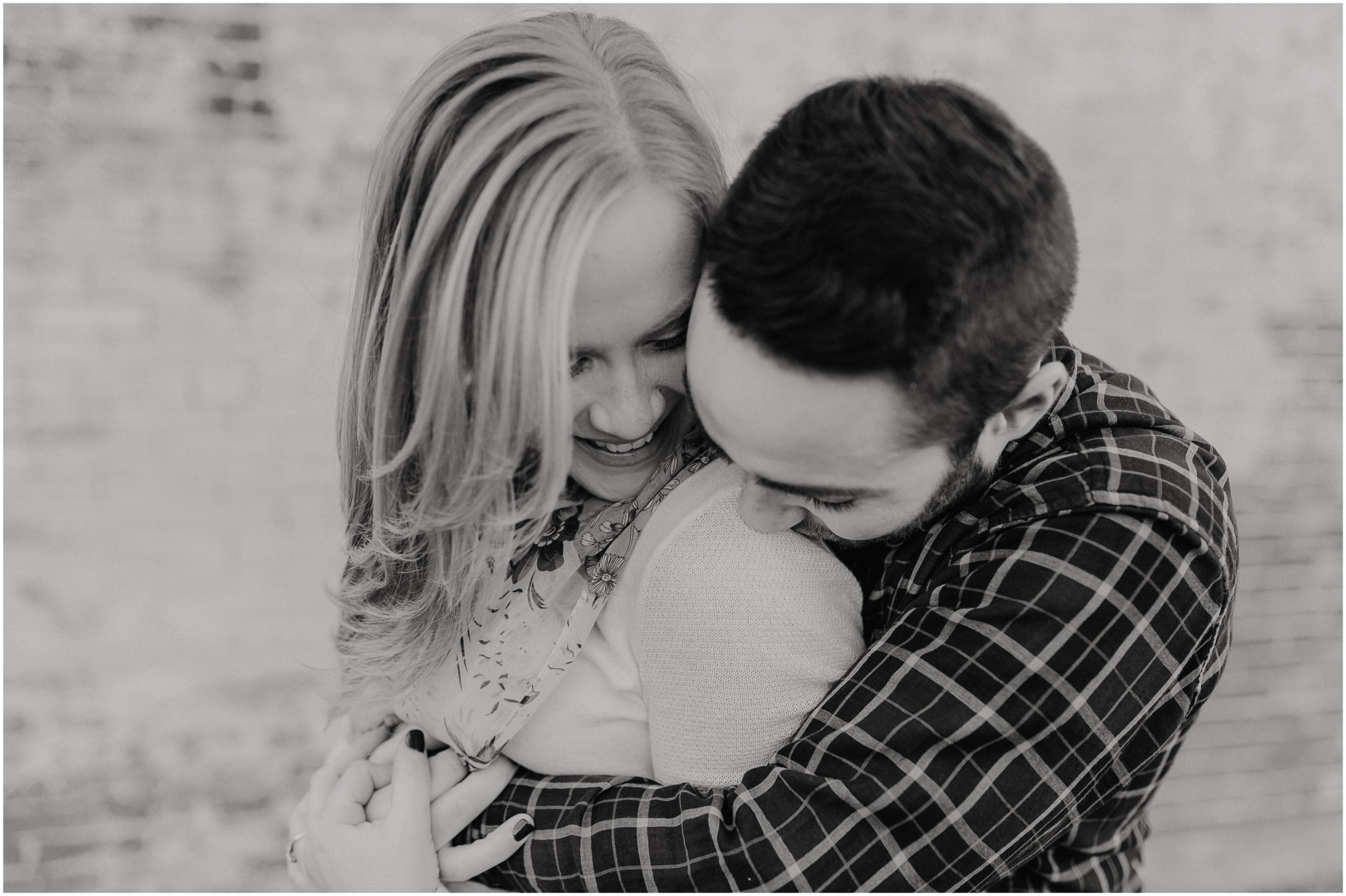 Man holds his fiancee close and kisses her shoulder for the engagement photos