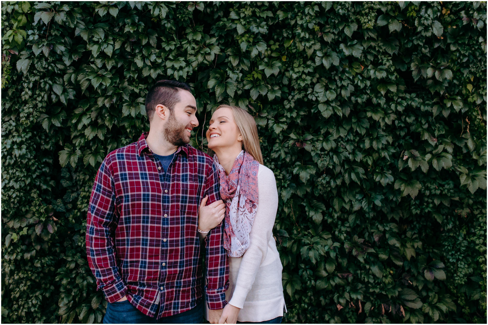 Beautiful couple laughs happily in front of a wall of ivy for the New England engagement photos - by New Hampshire wedding photographer Ashleigh Laureen Photography in Lowell, Massachusetts