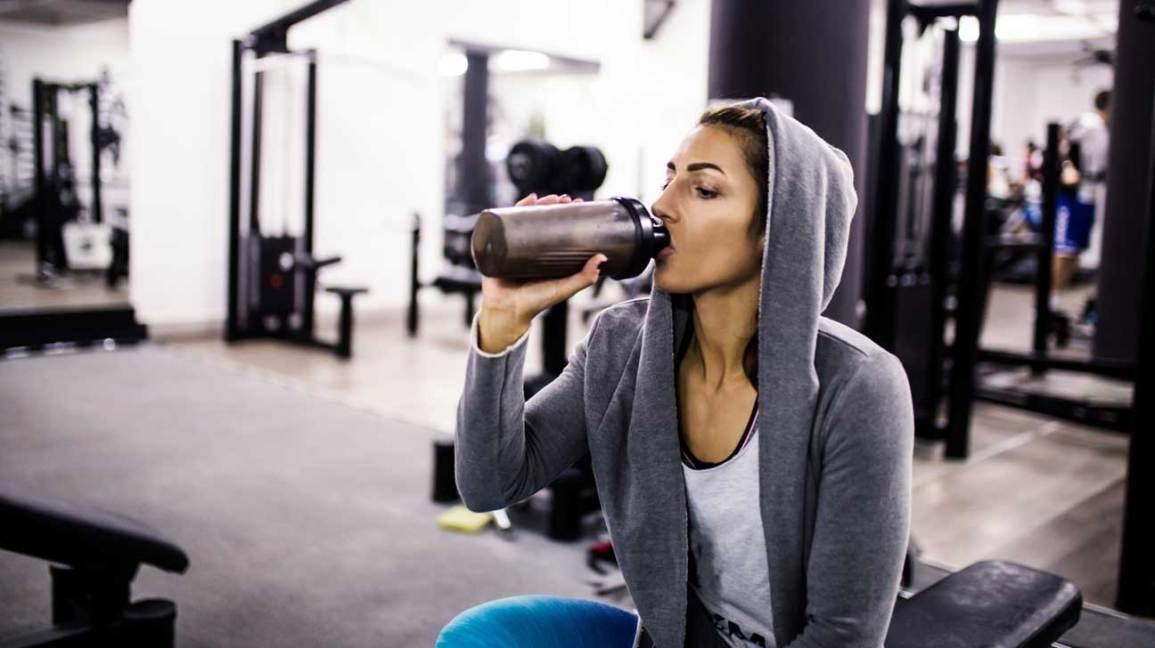 woman-in-gym-drinking-protein-shake-1296x728.jpg