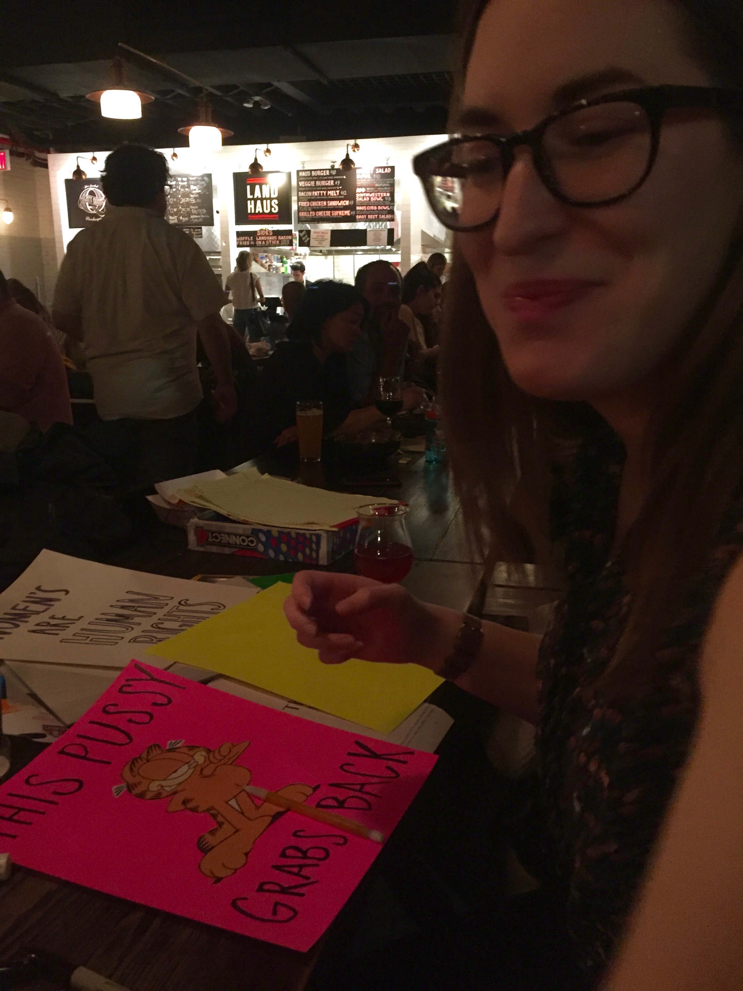 """Katie Madges working on a """"pussy grabs back"""" poster"""