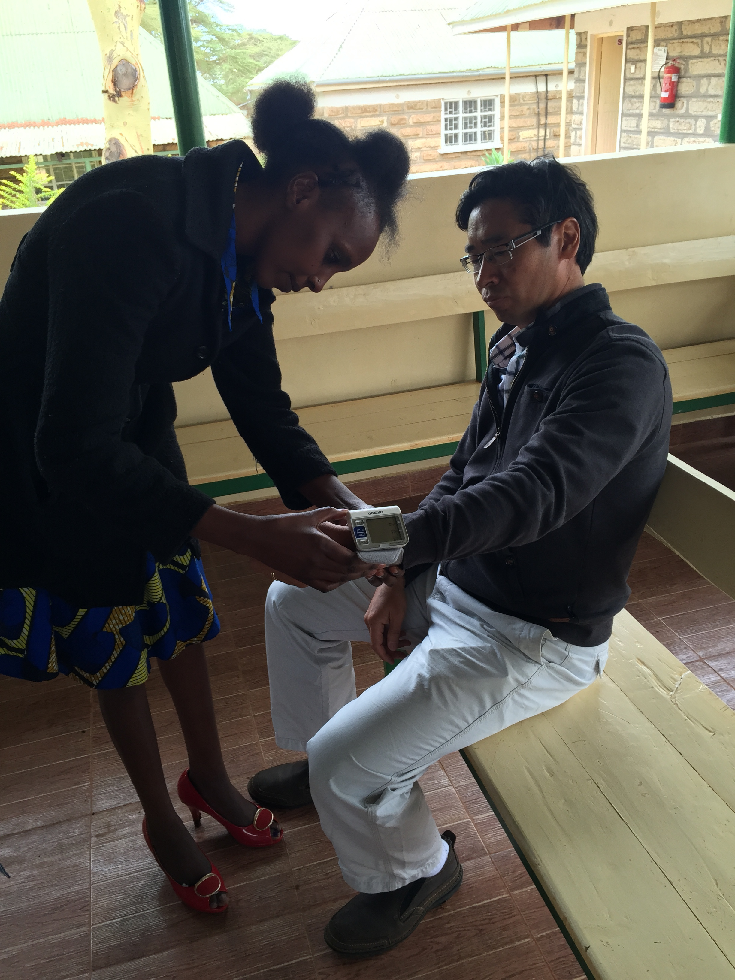 Emily, the community health worker, practising taking blood pressure on Dr. James Aw.