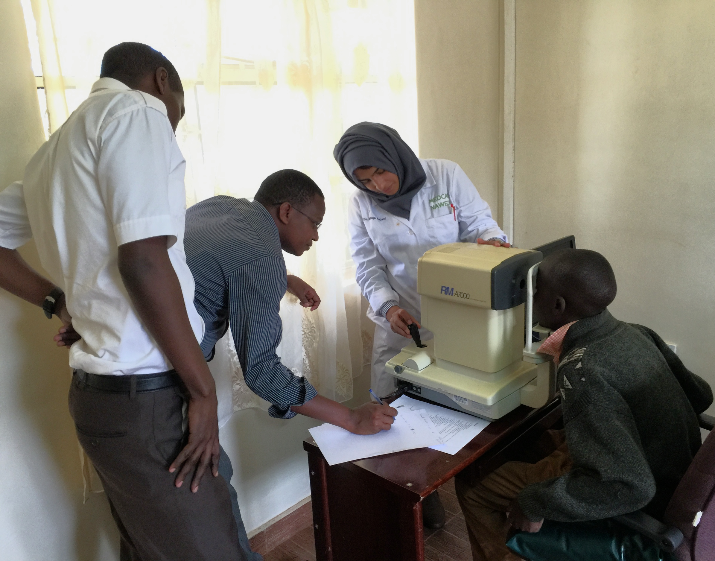 Dr. Sidiqa with Ezekiel and Geoffrey training on the auto-refractor.