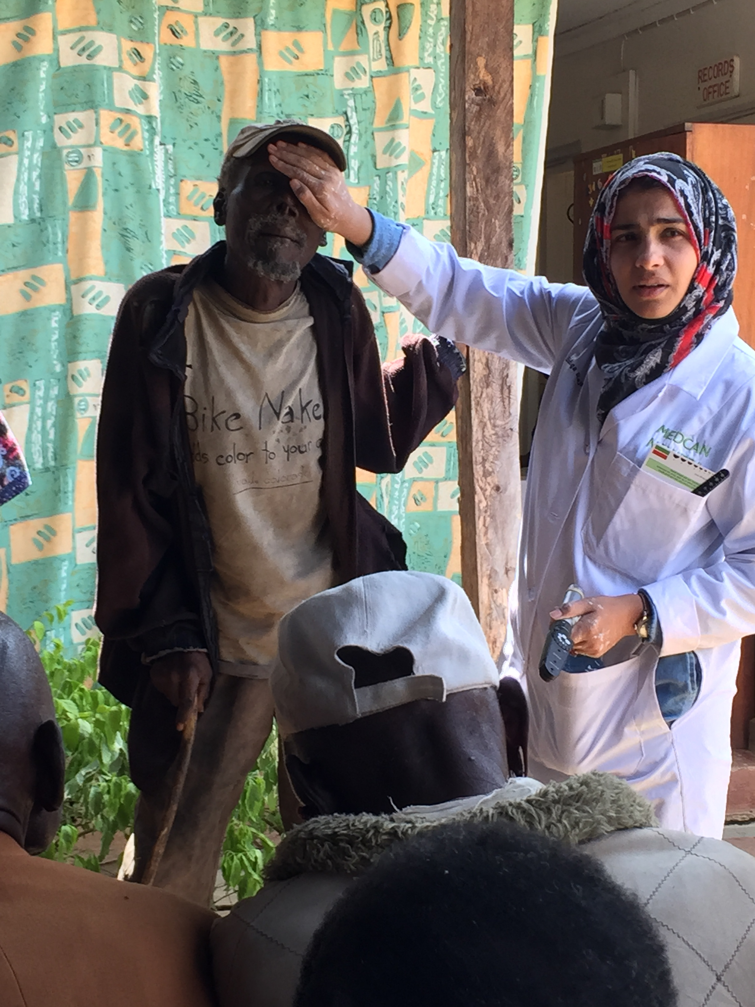 Dr. Sidiqa conducting a post-op vision check on a patient. This man has done quite well with much improved eye sight.