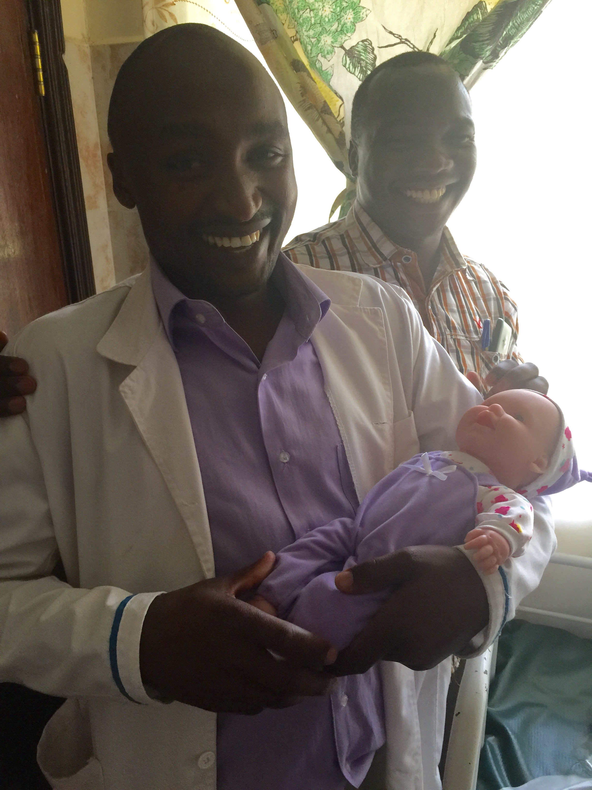 A fun moment with clinical officers Julius and Noah who are holding the baby prop for the Helping Babies Breathe course.