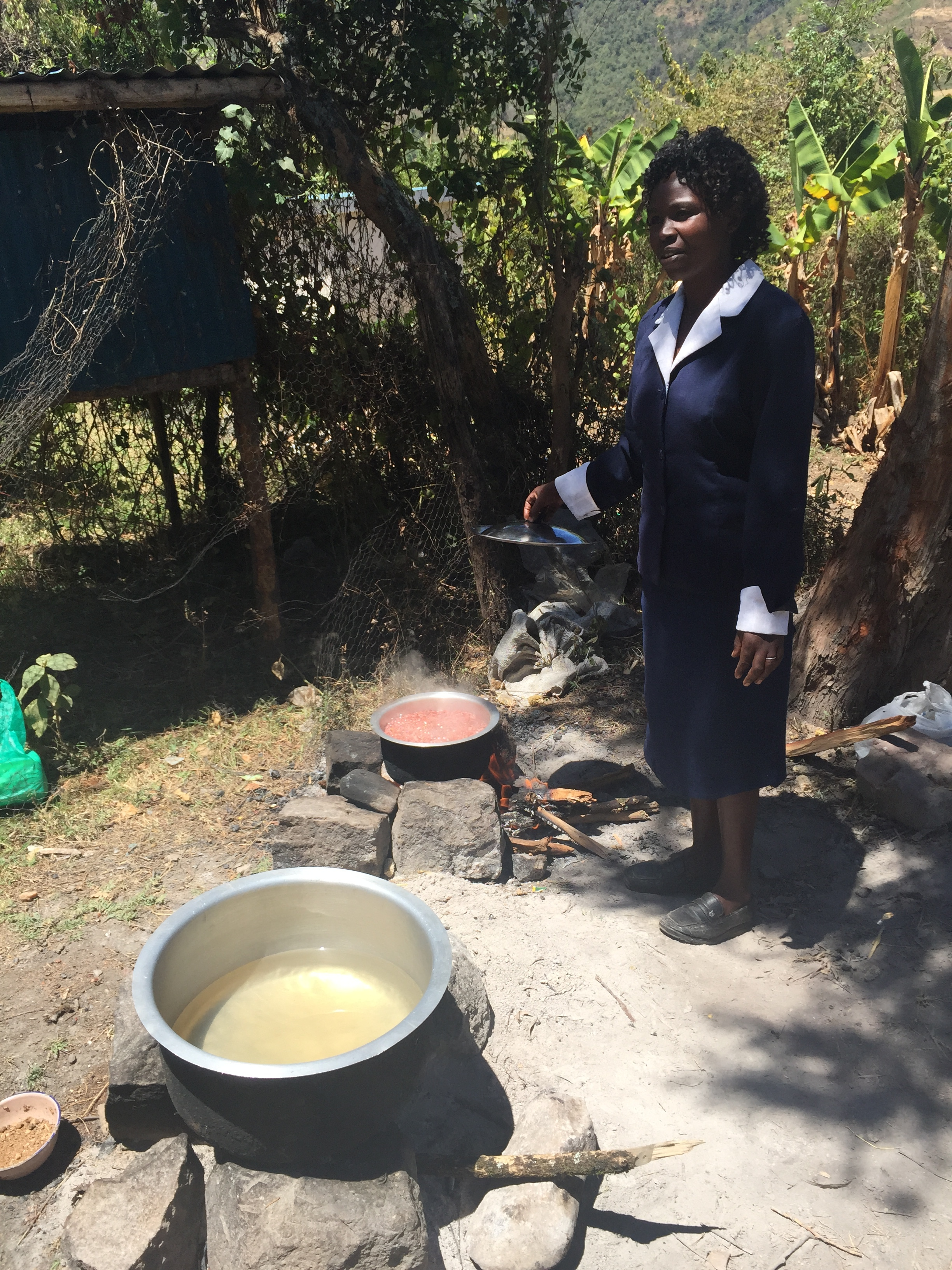 The teacher of the nursery school explains the cooking pots. One for rice and the other for beans.