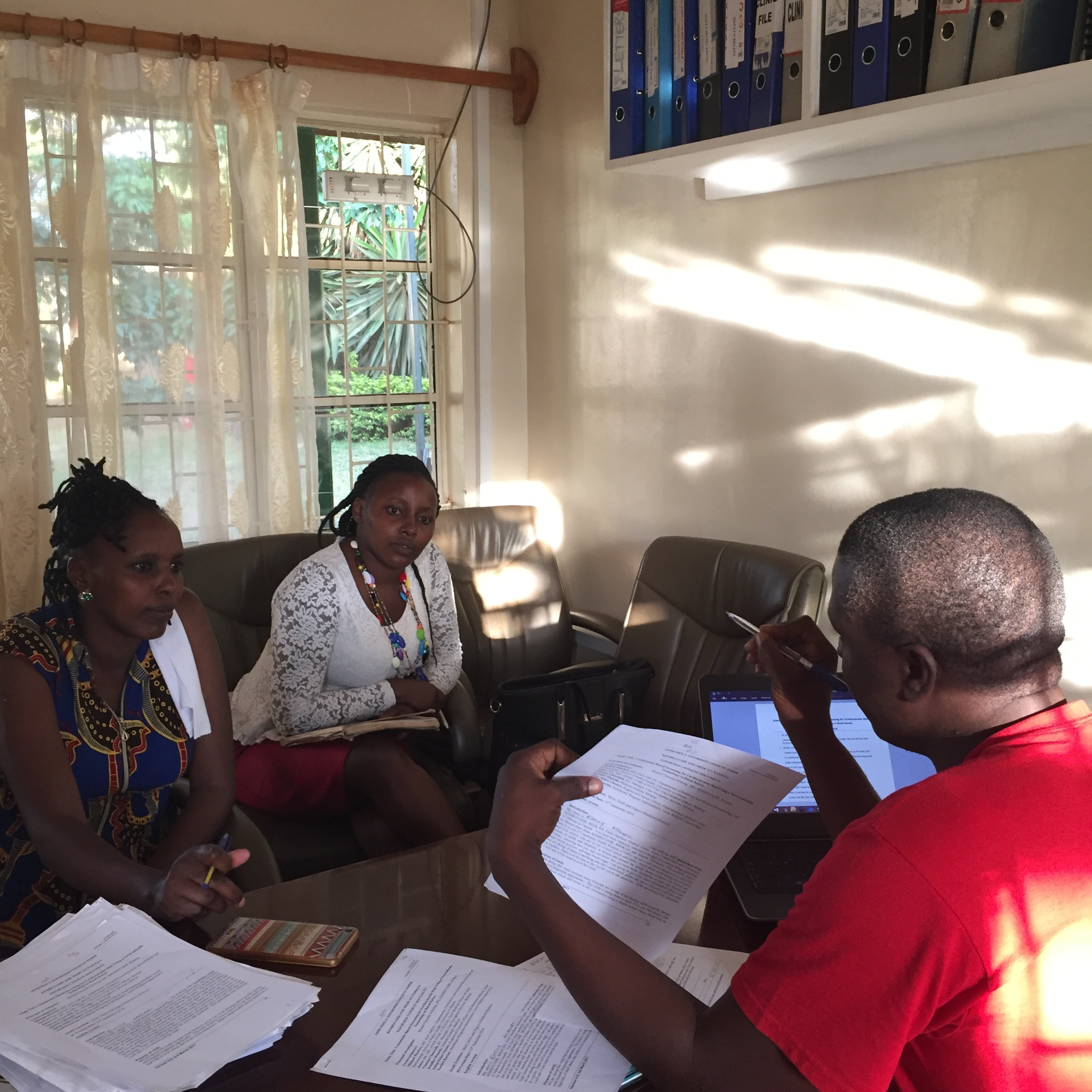 Emily, the community health worker, sits with Benard and