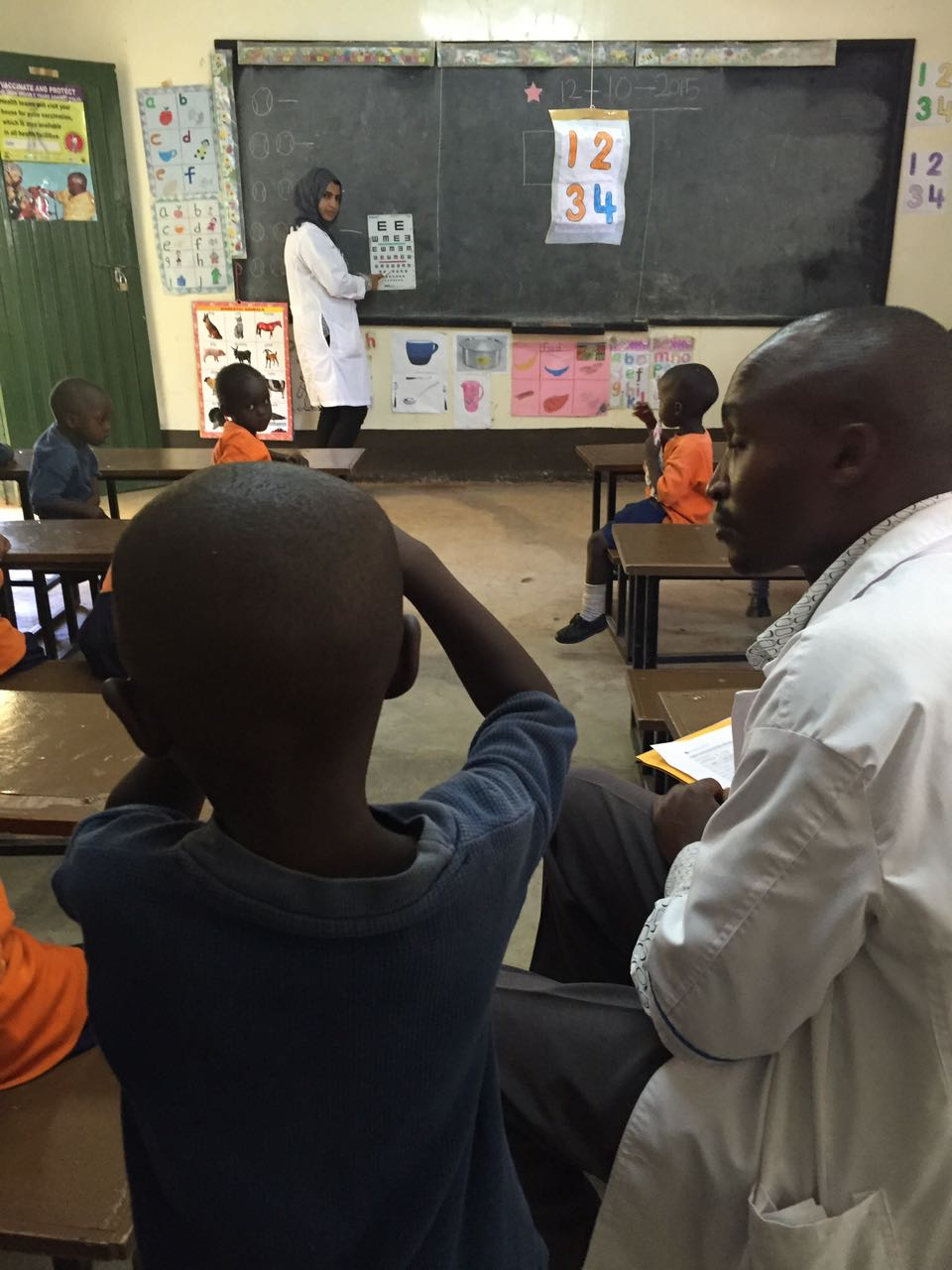 Dr. Sidiqa and the chalkboard while a young student performs an eye examination