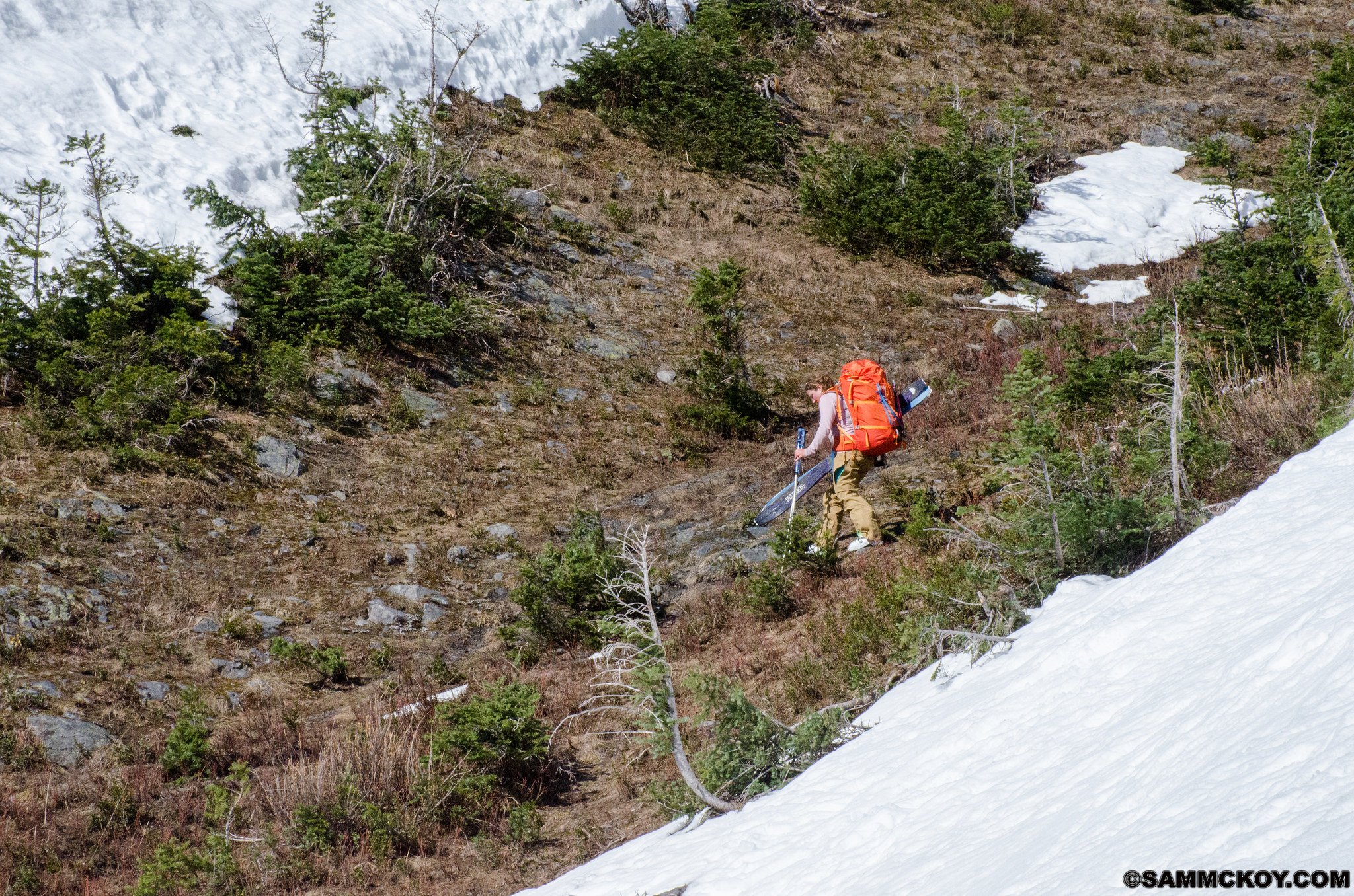 Madeleine crosses an avalanche path that's been stripped of snow.