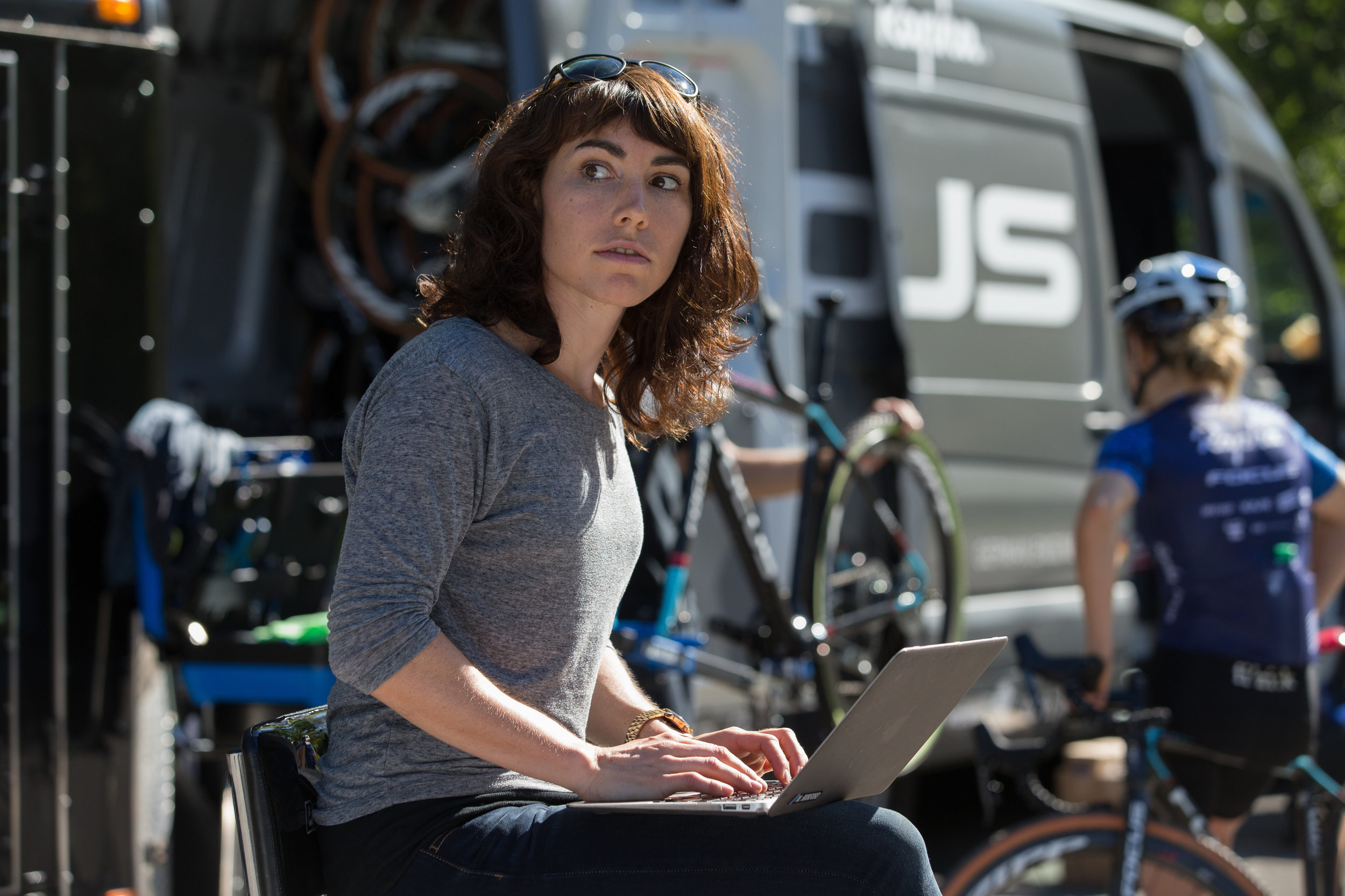 Molly working simultaneously on being a reporter and being a team manager, at a race with team Aspire Racing. Photo by Wil Matthews