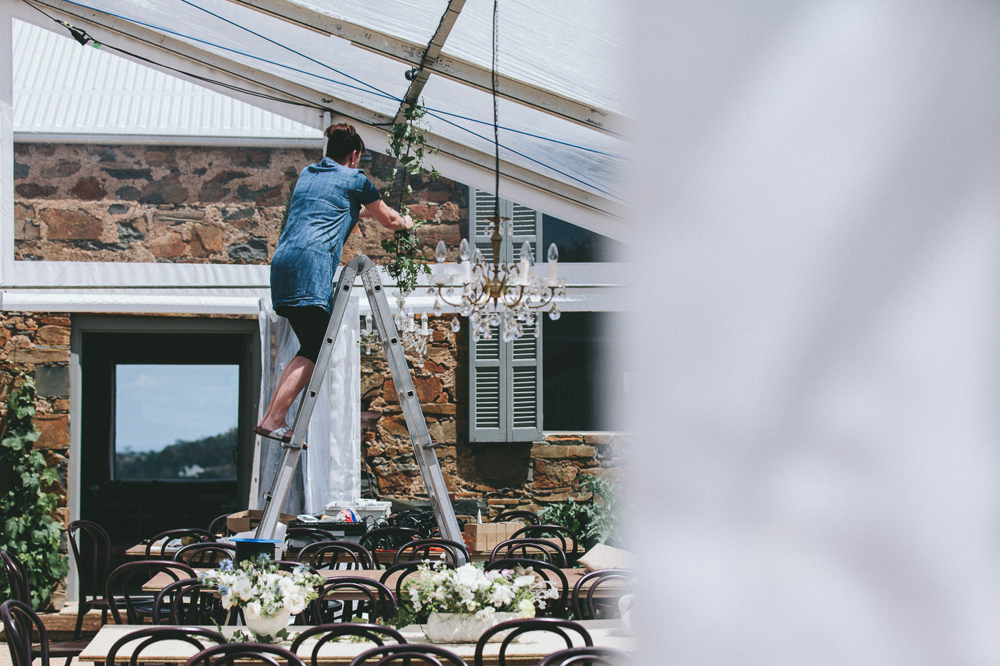 Stylist at work in a clear marquee on a property wedding