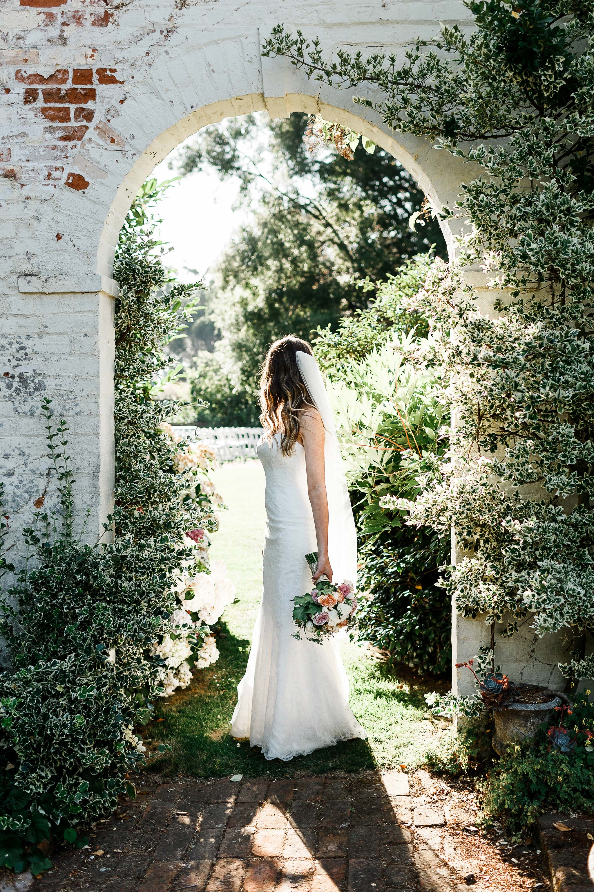 Bride under Brickendon homestead garden arch with bouquet