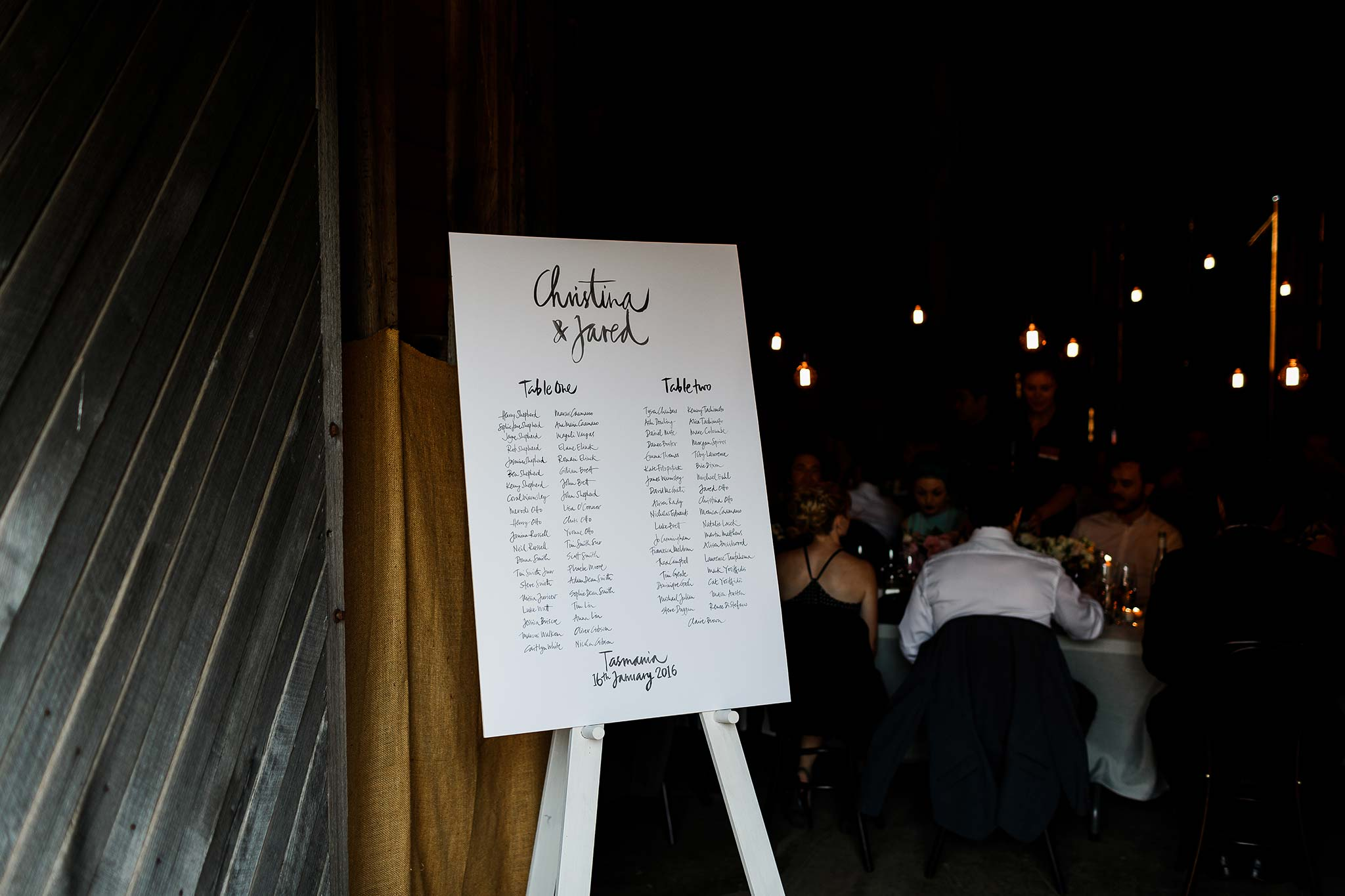 Hand written guest seating plan at the entry to the barn
