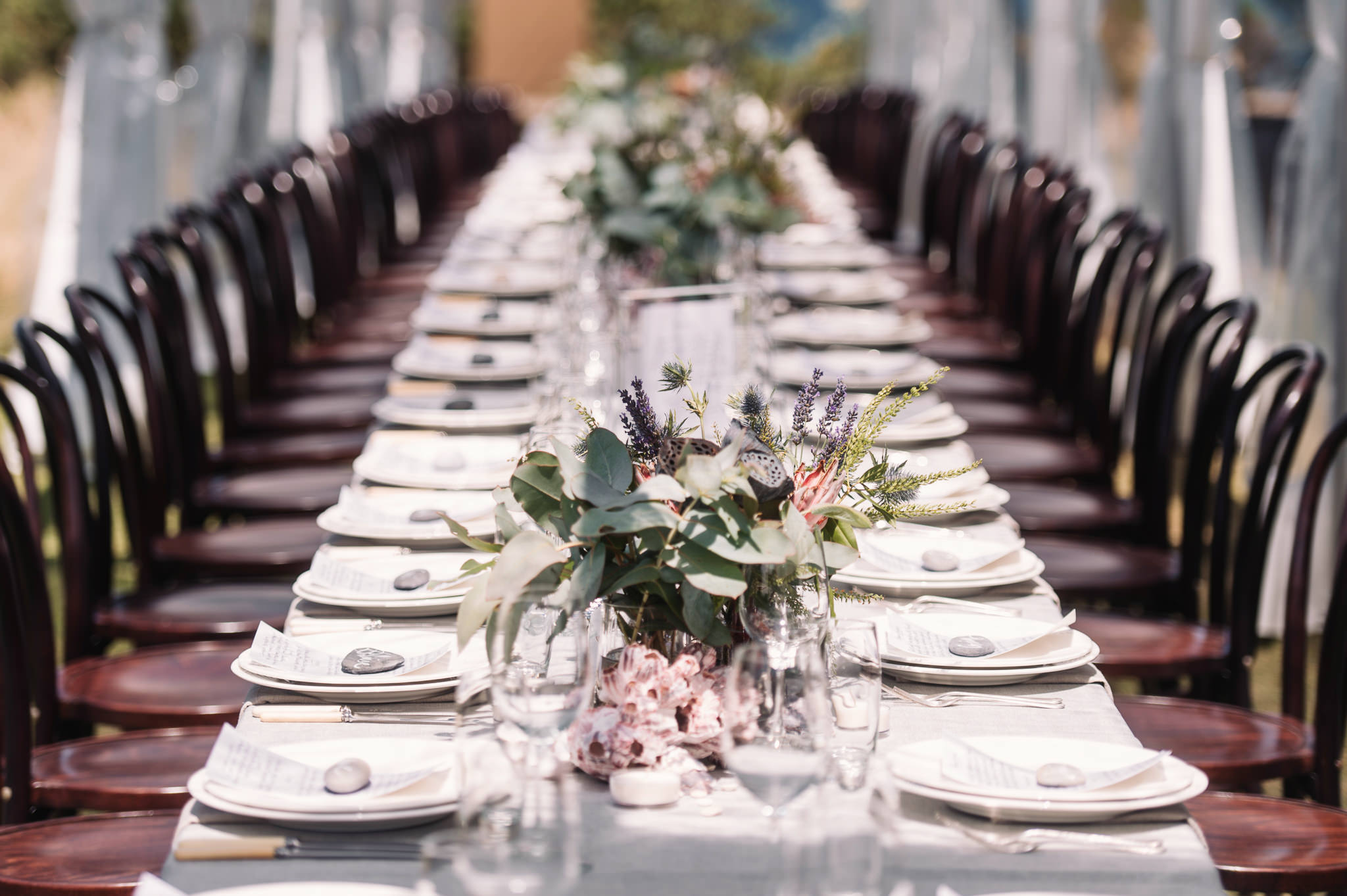 Long table set at Avalon Coastal retreat under a clear marquee