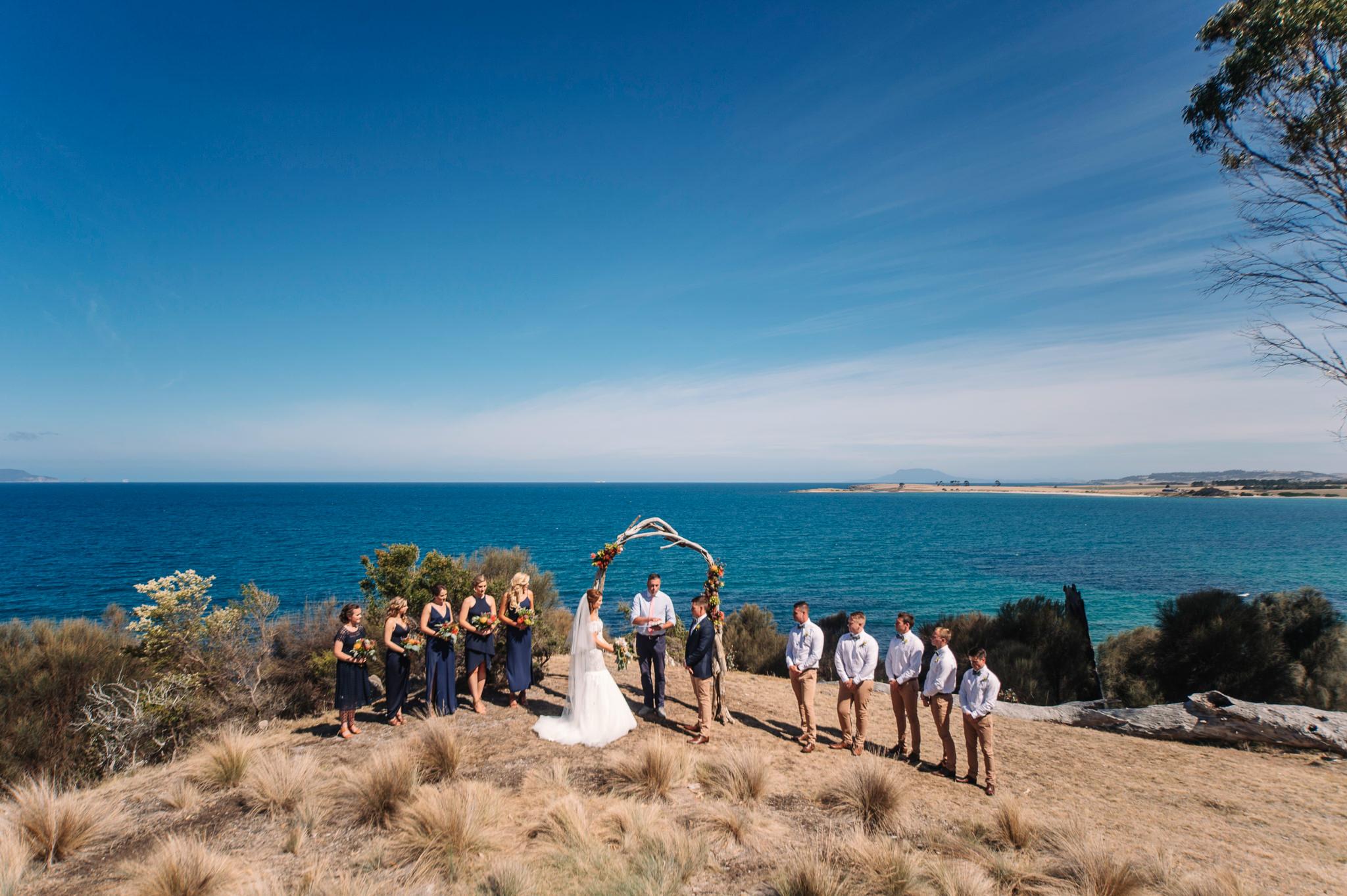 Wedding Ceremony under a driftwood arch at Avalon Coastal retreat