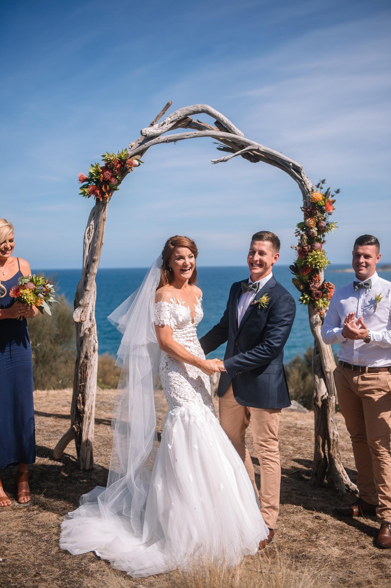 Coastal wedding under an arch of locally found driftwood