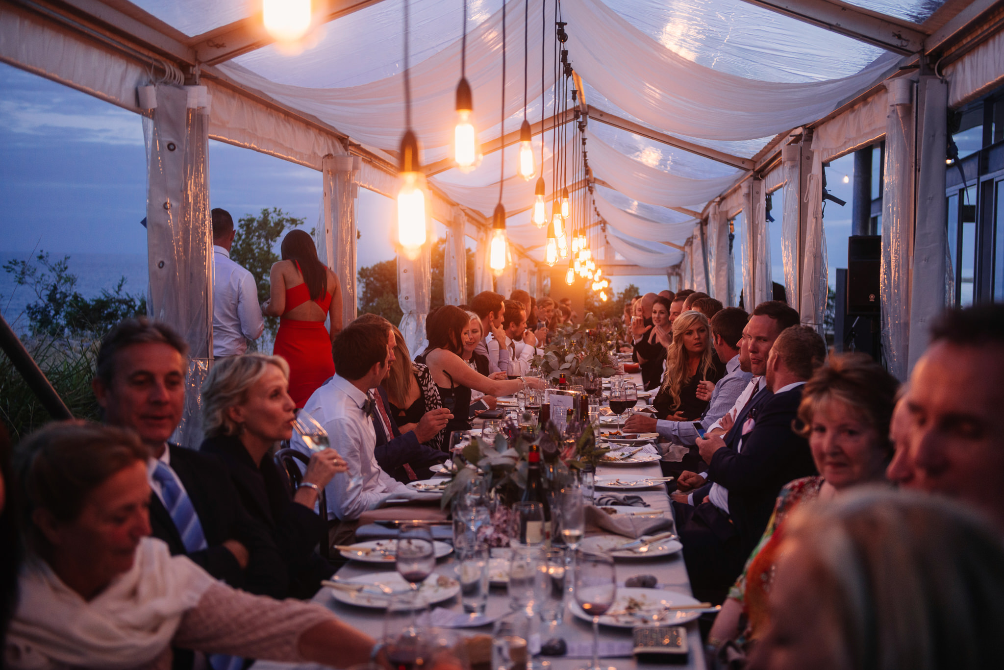 Long table in a clear marquee at Avalon Coastal Retreat