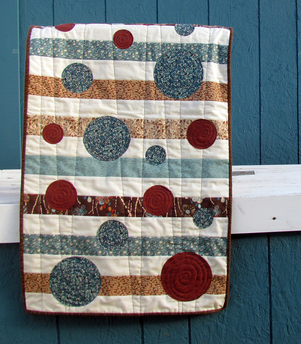 Bubbly Stripes by Chatterbox Quilts would look great in seasonal fabrics with decorative machine stitching around the appliquéd circles.