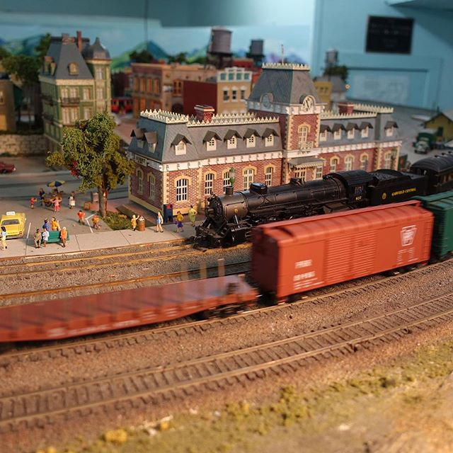Passengers linger waiting for the Garfield Central excursion train to board. A fast freight rushes by in the mean time. #hoscale #modeltrain #modeltrains #modelrailroad #modelrailroading #garfieldcentralrailroad #scalefigure