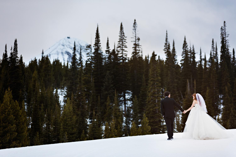 big-sky-montana-winter-wedding-breanna-first-look-bride-groom-walking-over-snow.jpg