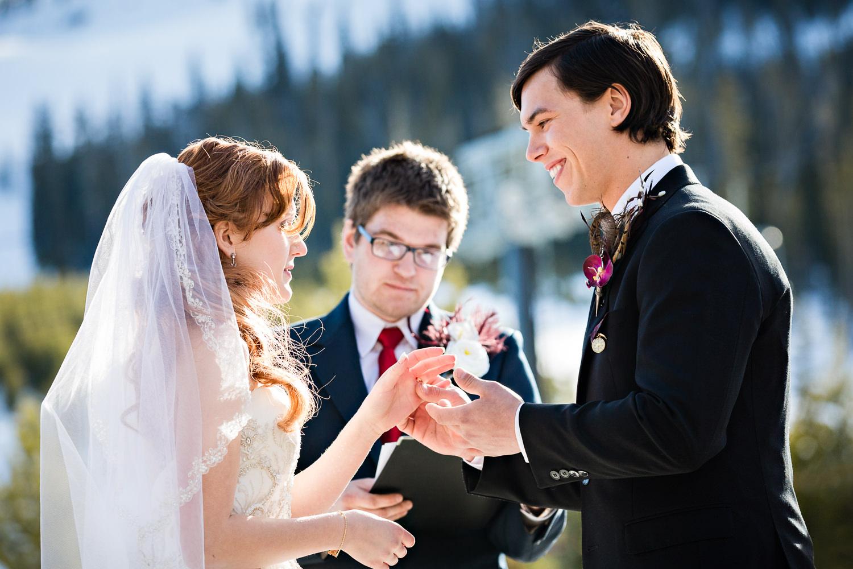 big-sky-montana-winter-wedding-breanna-ceremony-groom-exchanges-rings.jpg