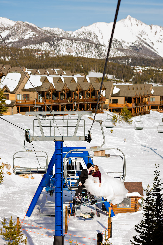 big-sky-montana-winter-wedding-breanna-formals-bride-groom-kiss-on-chairlift.jpg