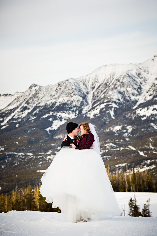 big-sky-montana-winter-wedding-breanna-formals-groom-lifts-bride-for-kiss.jpg