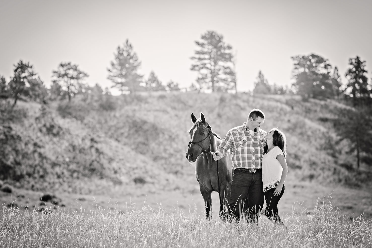 billings-montana-engagement-session-happy-couple-in-field-with-their-horse-back-and-white.jpg