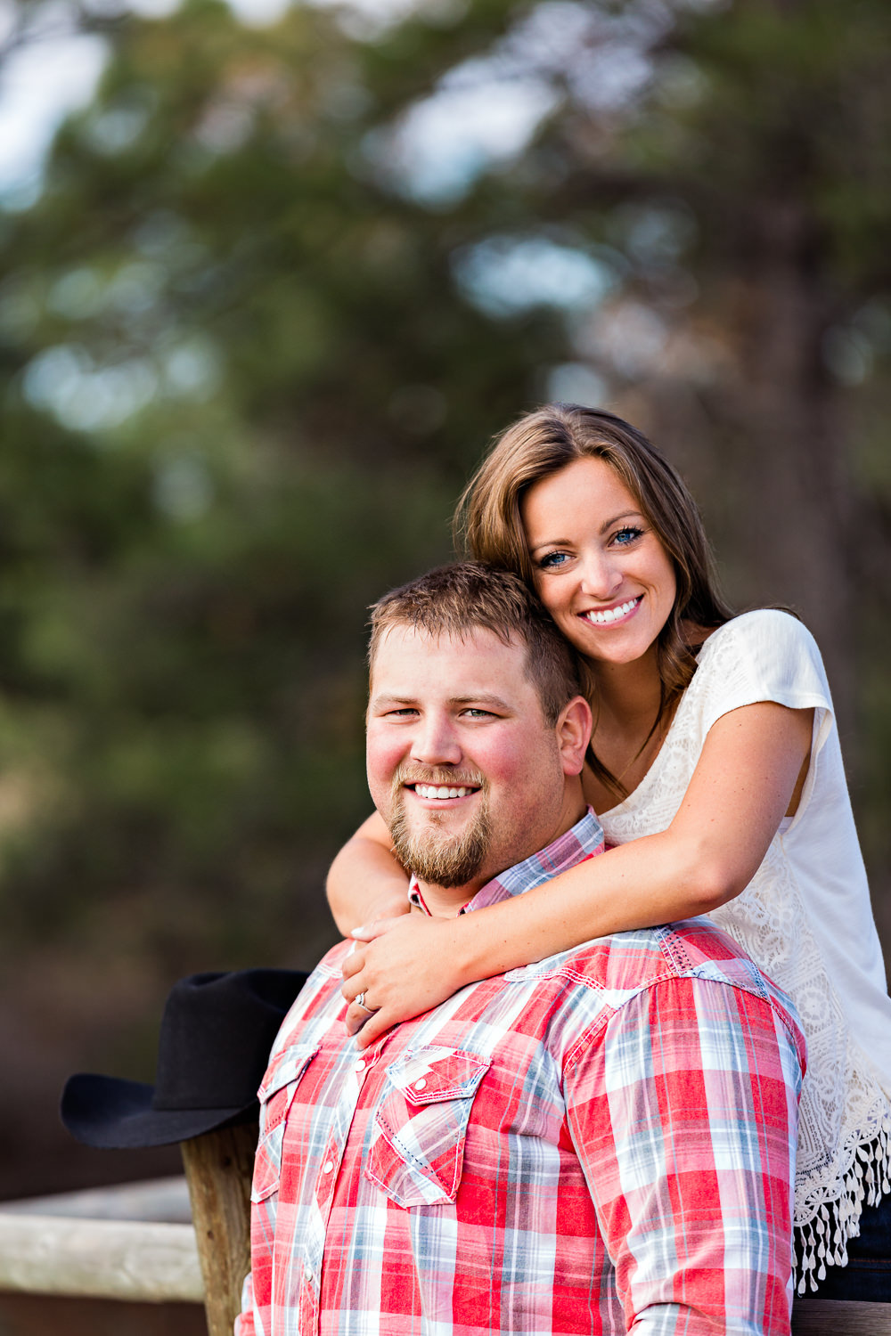 billings-montana-engagement-session-woman-stands-on-fence-behind-man.jpg