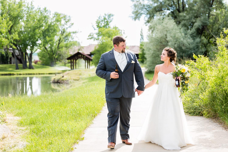 billings-montana-swift-river-ranch-wedding-reception-couple-walks-with-beer.jpg