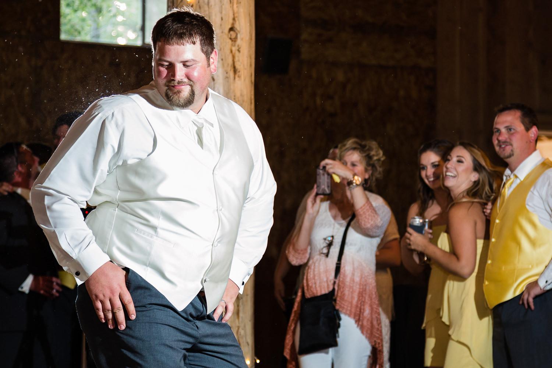 billings-montana-swift-river-ranch-wedding-reception-groom-makes-moves-before-garter-toss.jpg