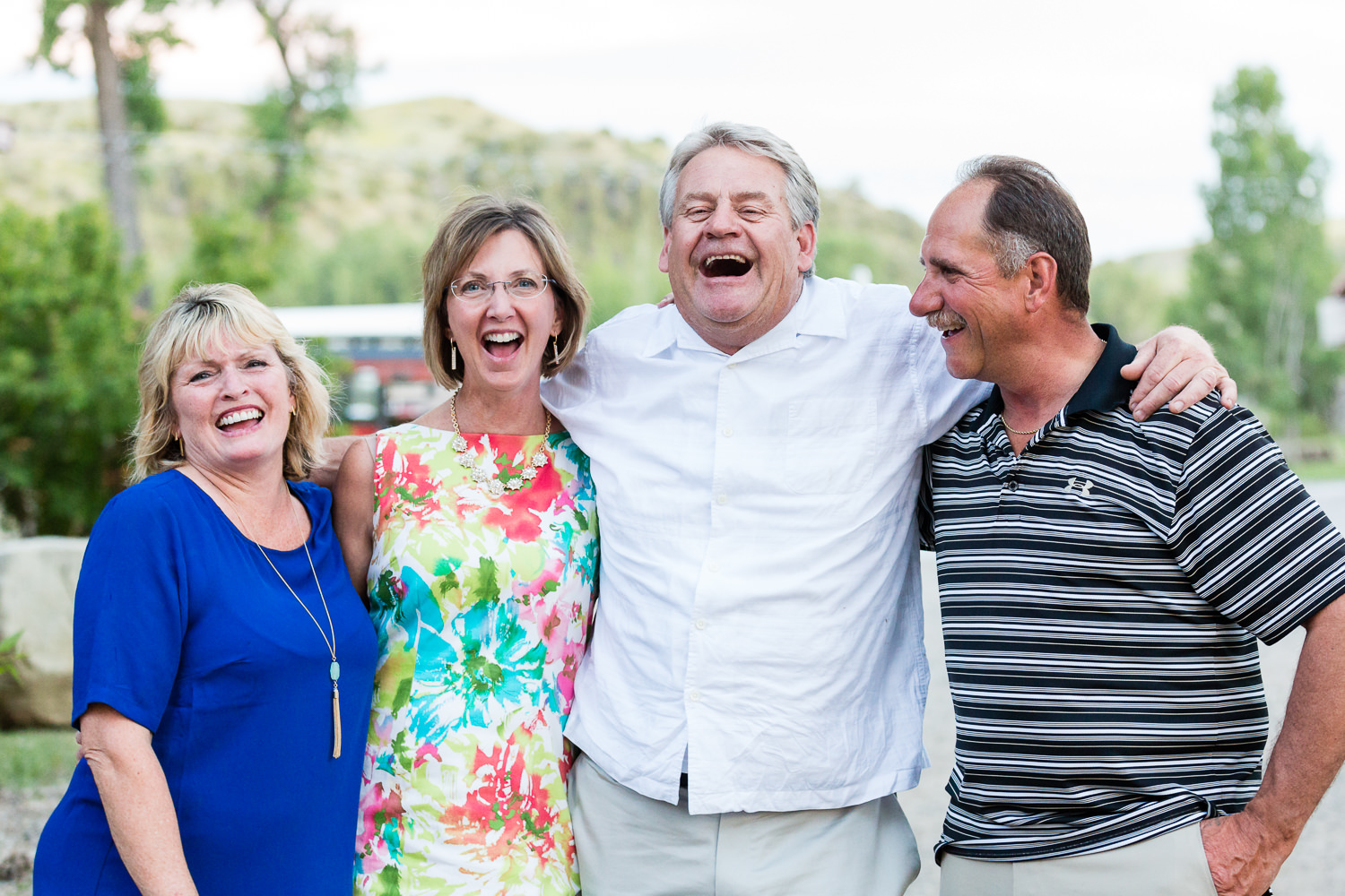 billings-montana-swift-river-ranch-wedding-reception-guests-laughing-at-sunset.jpg