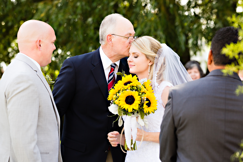 bozeman-montana-wedding-roys-barn-father-kisses-daughter-during-ceremony.jpg