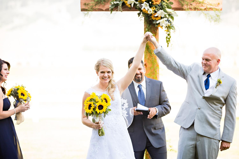 bozeman-montana-wedding-roys-barn-recessional-bride-groom-raise-hands.jpg
