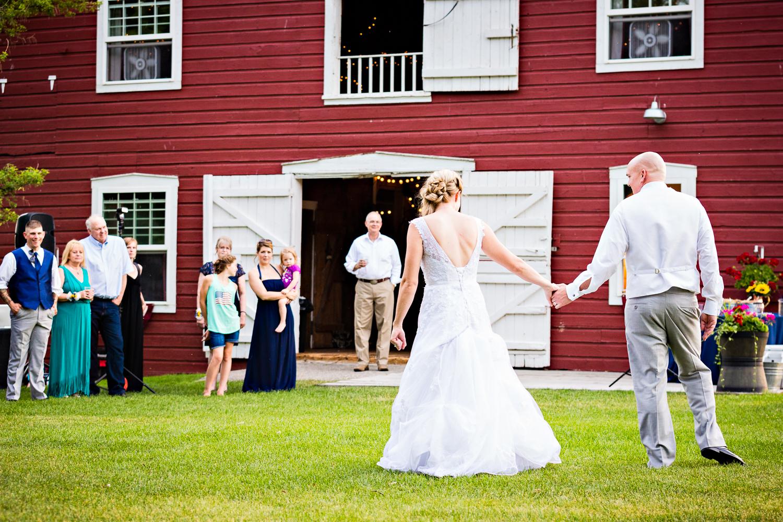 bozeman-montana-wedding-roys-barn-bride-groom-hold-hands-during-reception.jpg