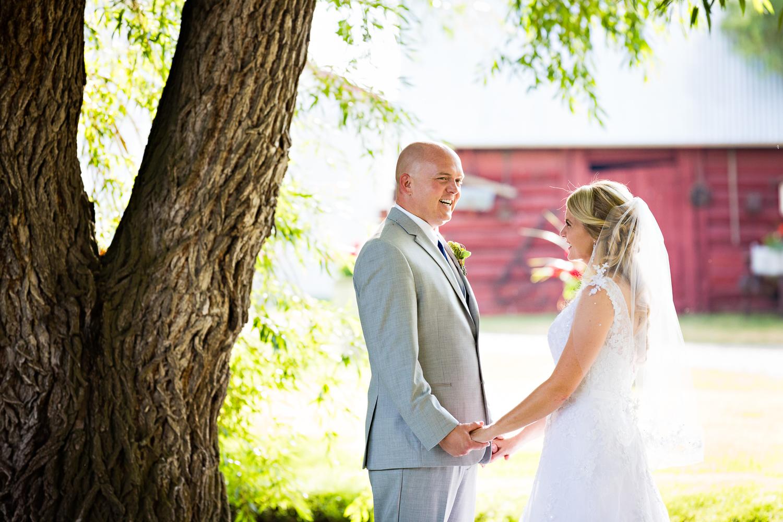 bozeman-montana-wedding-roys-barn-bride-groom-laugh-hold-hands.jpg