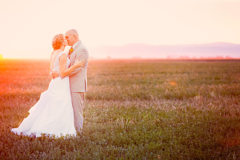 bozeman-montana-wedding-roys-barn-couple-kisses-under-orange-sunset.jpg
