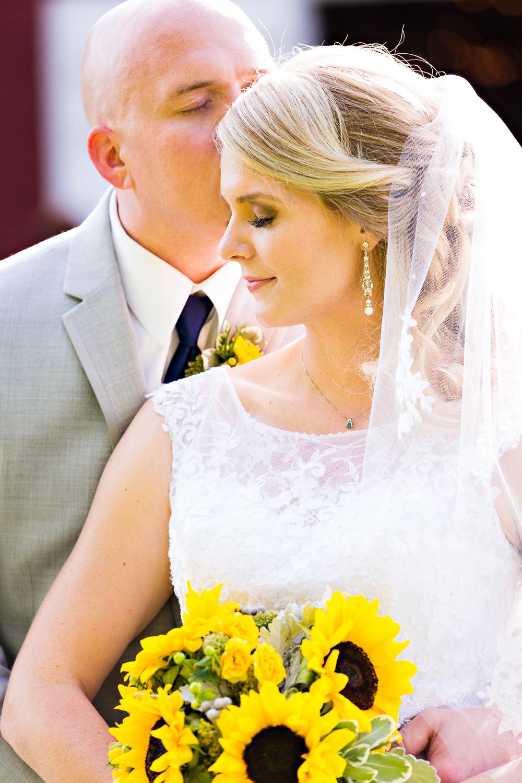 bozeman-montana-wedding-roys-barn-groom-kisses-brides-forehead.jpg