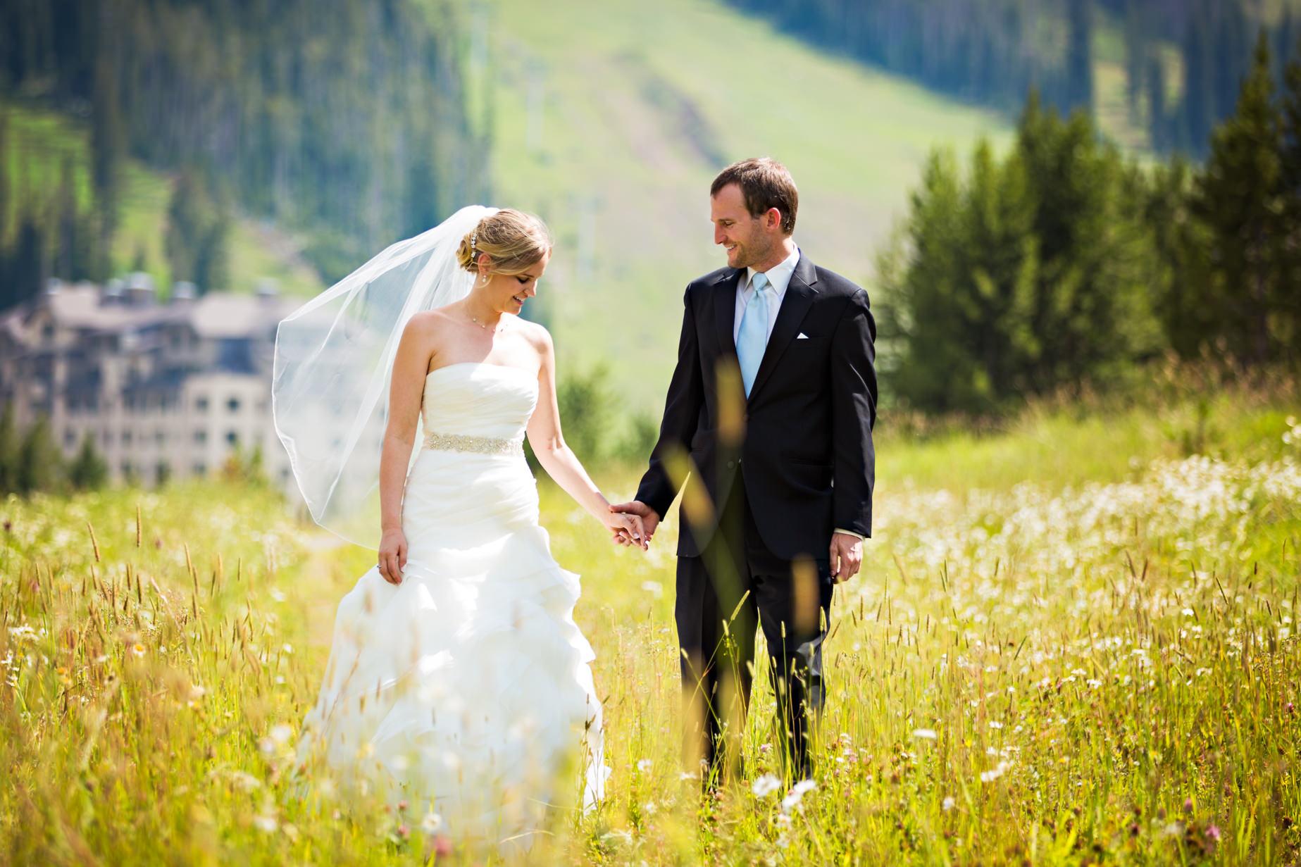 big-sky-resort-wedding-bride-groom-hold-hands-in-field.jpg