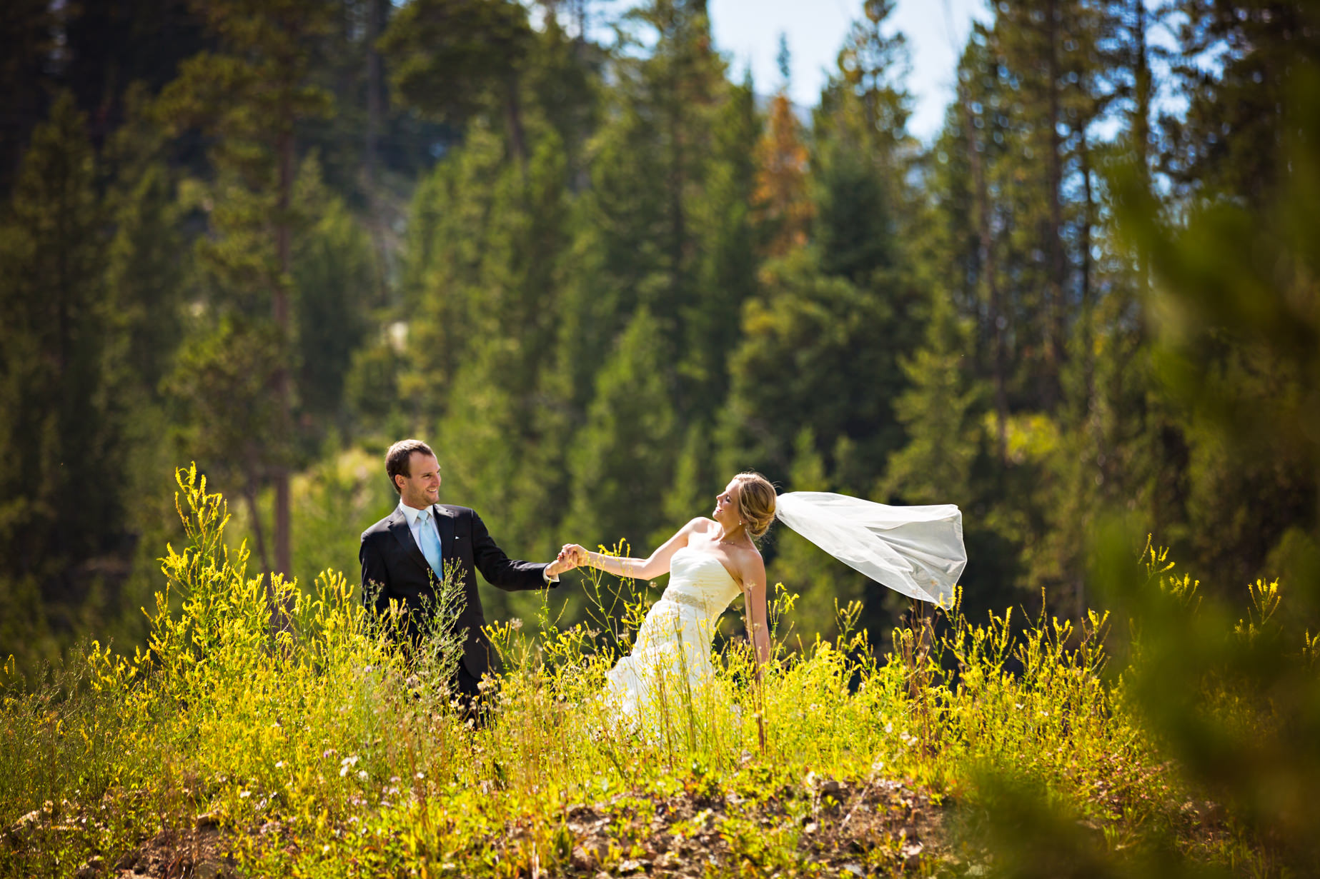 big-sky-resort-wedding-groom-pulls-brides-hand.jpg