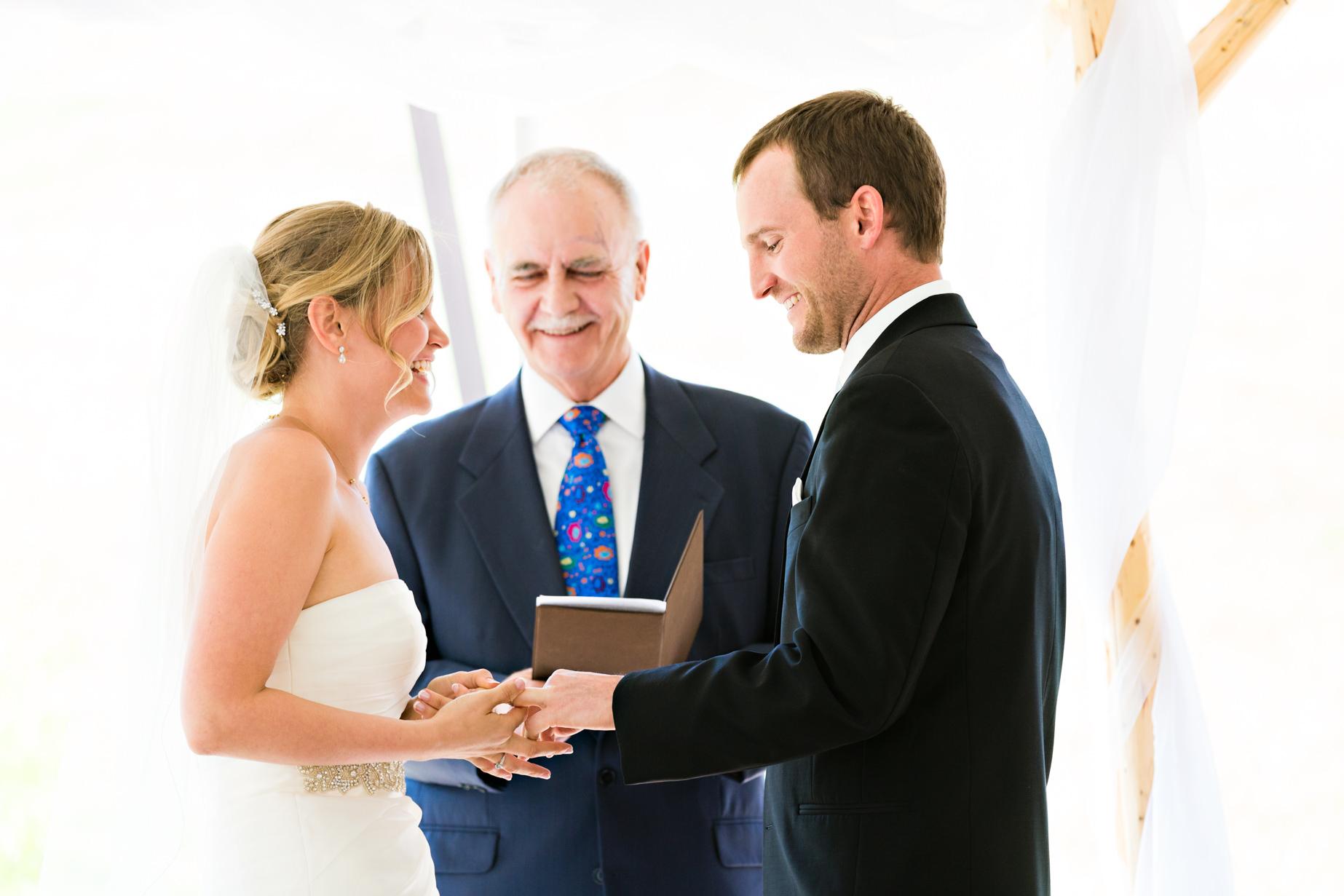 big-sky-resort-wedding-bride-groom-laugh-during-ring-exchange.jpg
